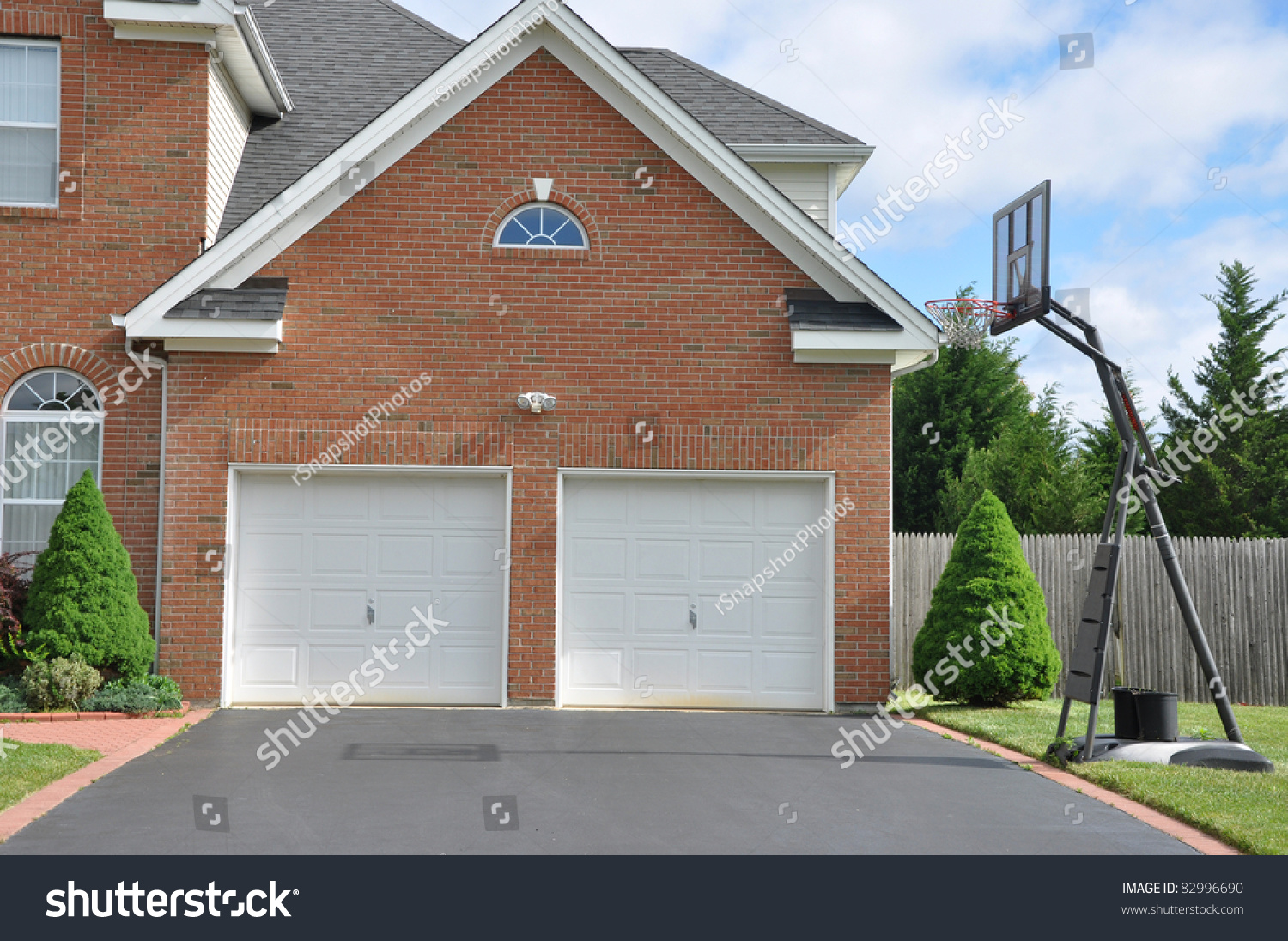 Basketball hoop on driveway front suburban stock photo for Basketball garage