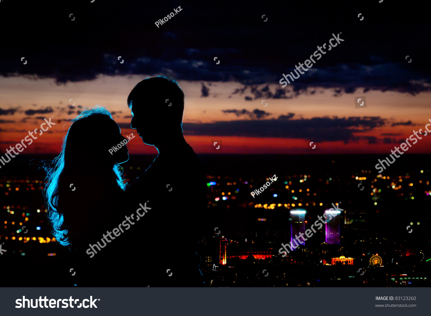 Silhouette of the holy cross on background of storm clouds stock - Young Couple Silhouette Hugging And Looking At Each Other Outdoors At Night Neon City Background
