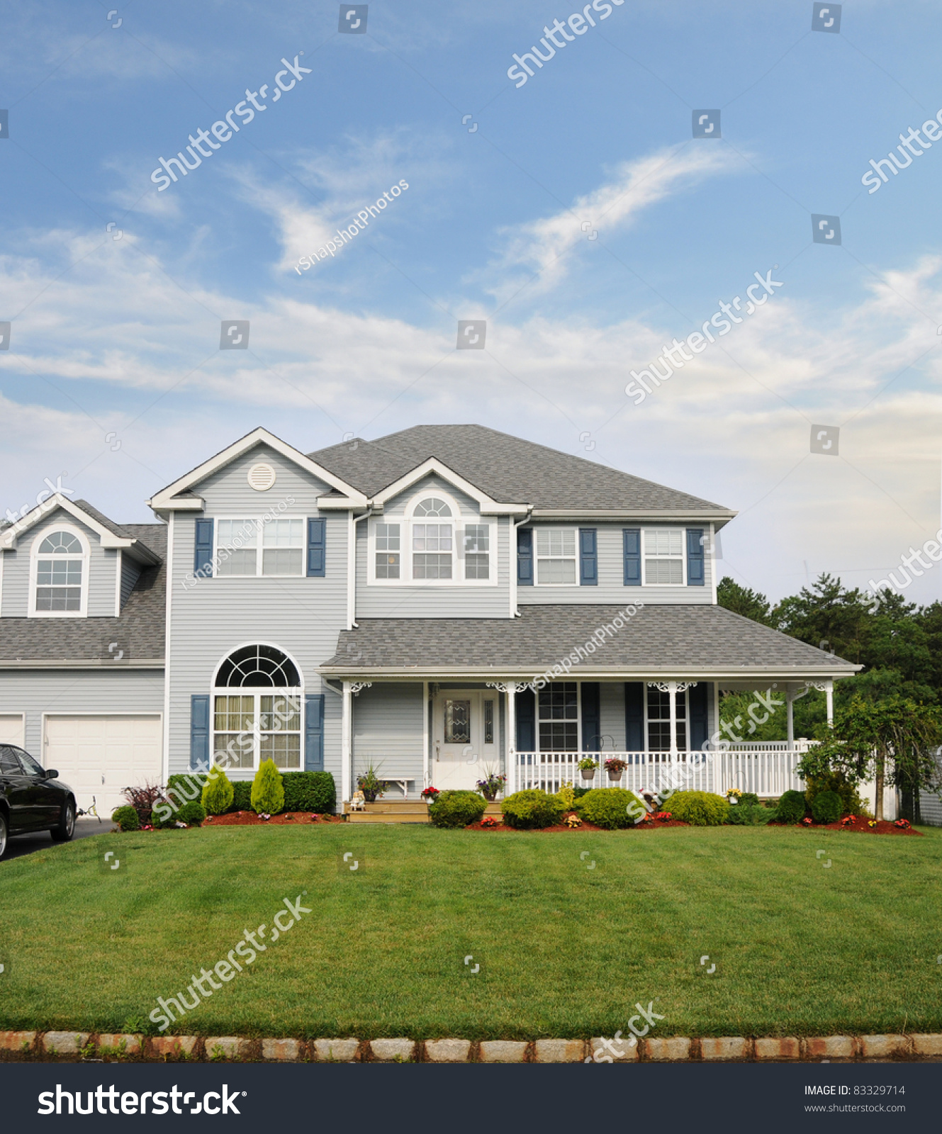 Suburban Two Story Home With Porch Landscaped Front Yard