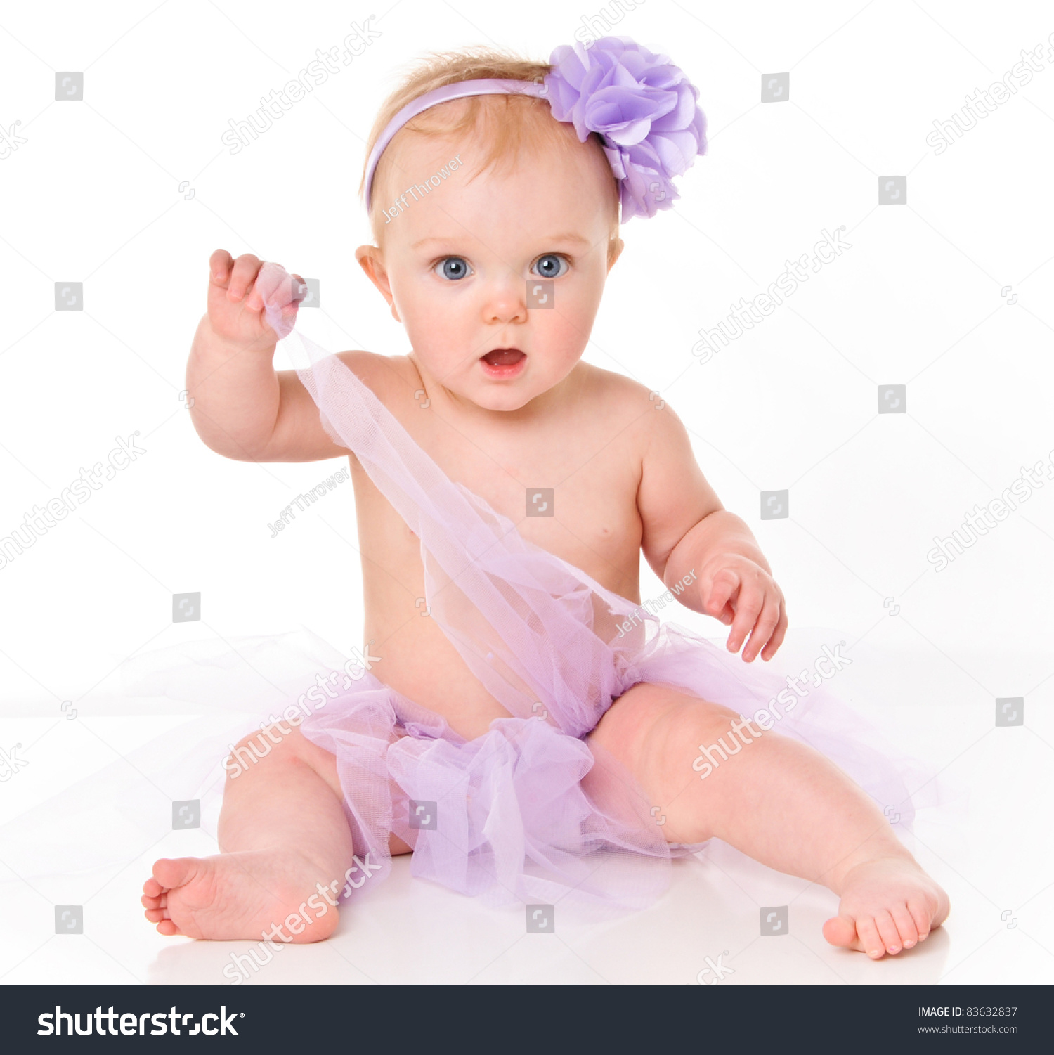 cute little baby girl with big blue eyes wearing a tutu and flower