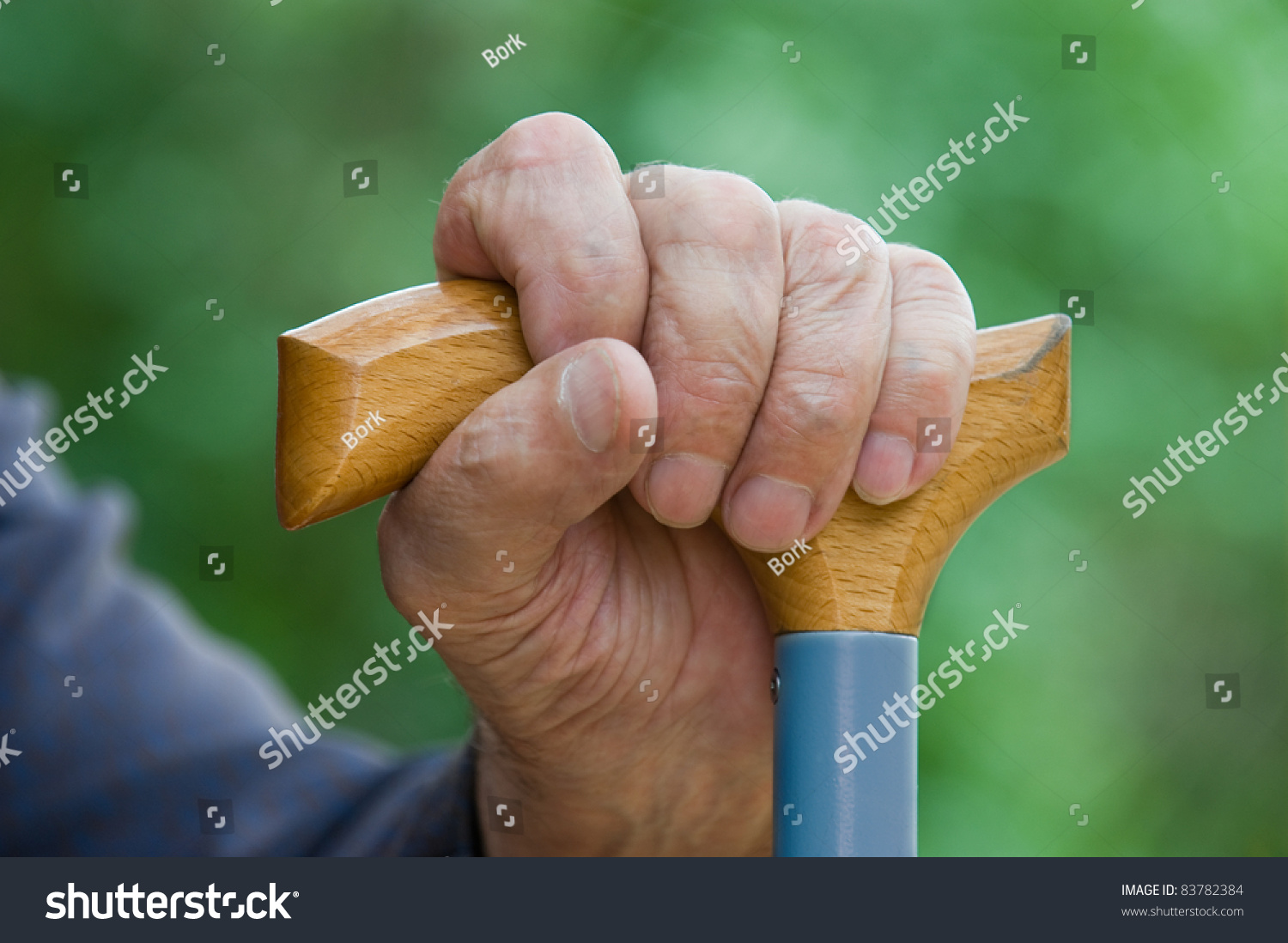 Hand Holding Stick ~ Old tired mans hand holding stick stock photo