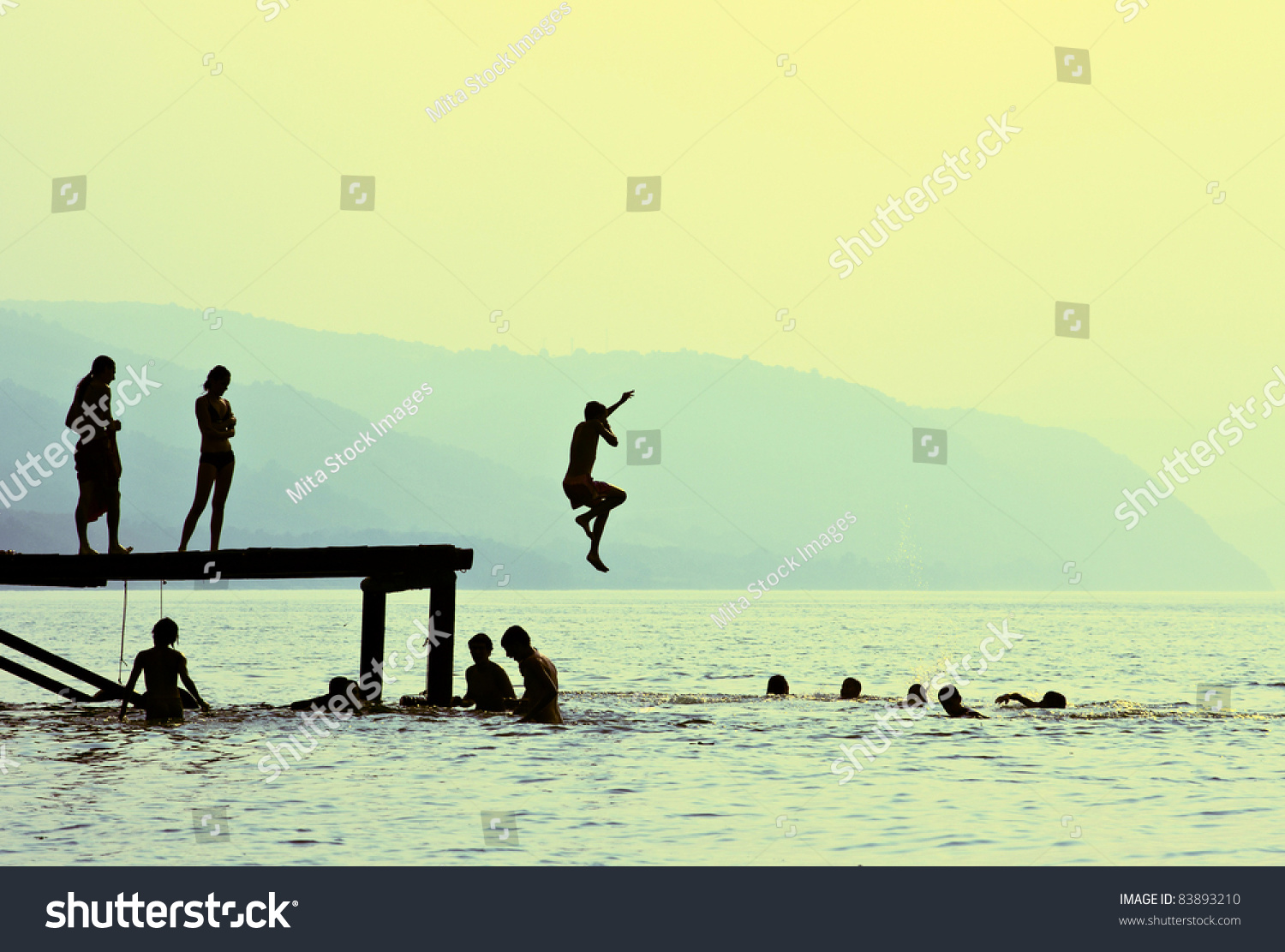Silhouettes Of Kids Who Jump Off Dock On The Lake At Sunset Stock Photo 83893210 Shutterstock