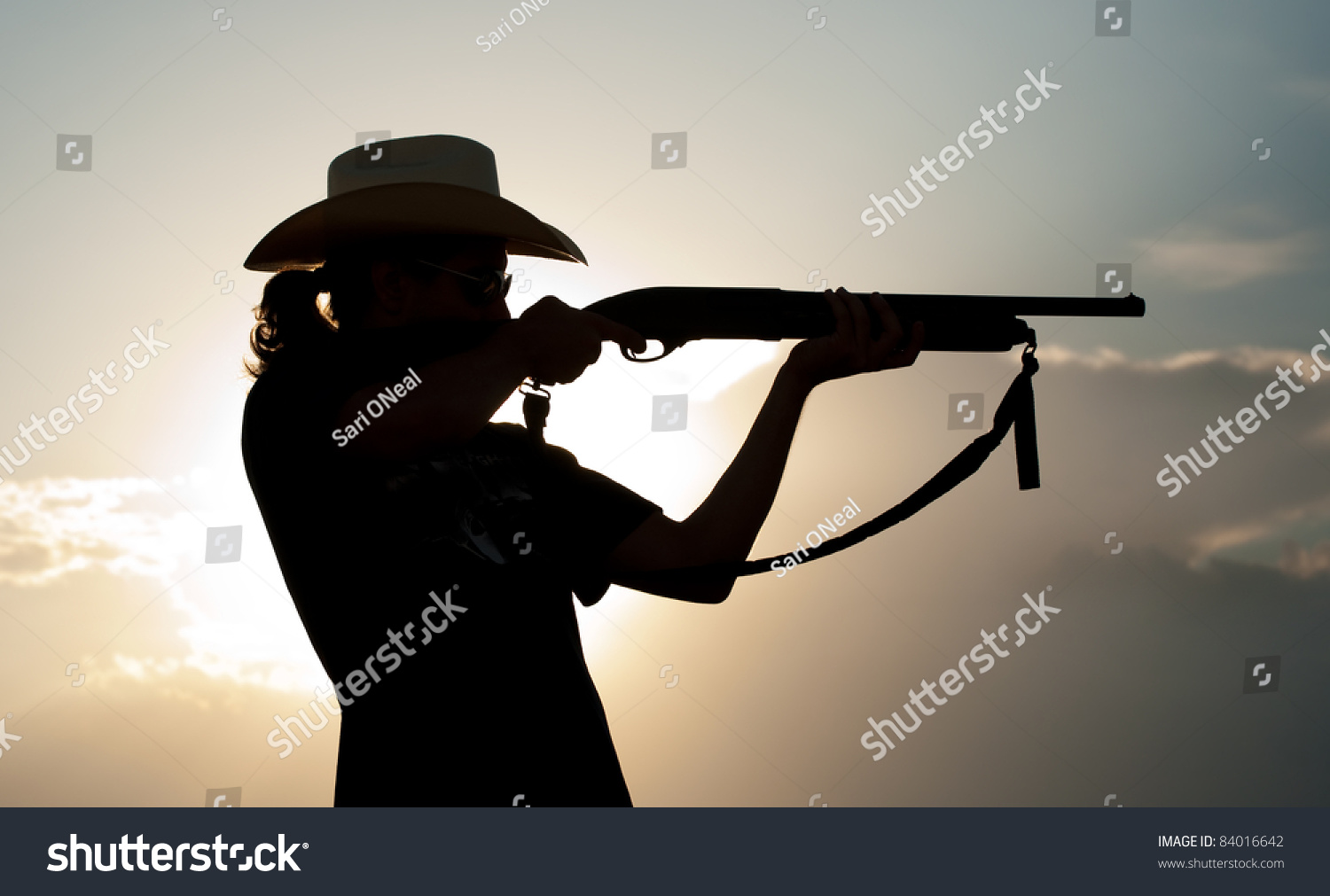 Silhouette Of A Young Man In A Cowboy Hat Shooting With A ...