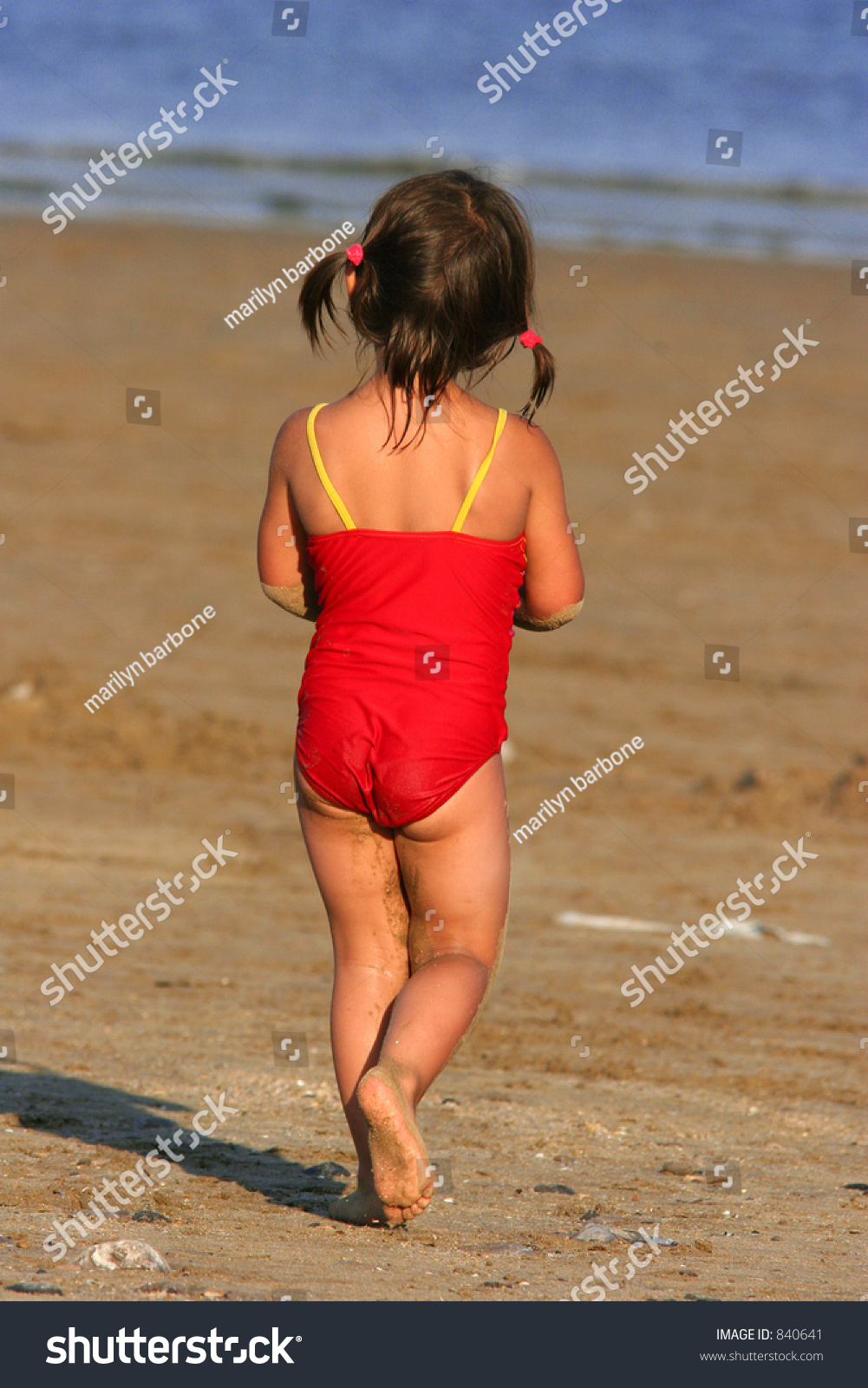 Little girl in bikini rear view Rear view of a little girl wearing a red swimsuit and walking on the beach.