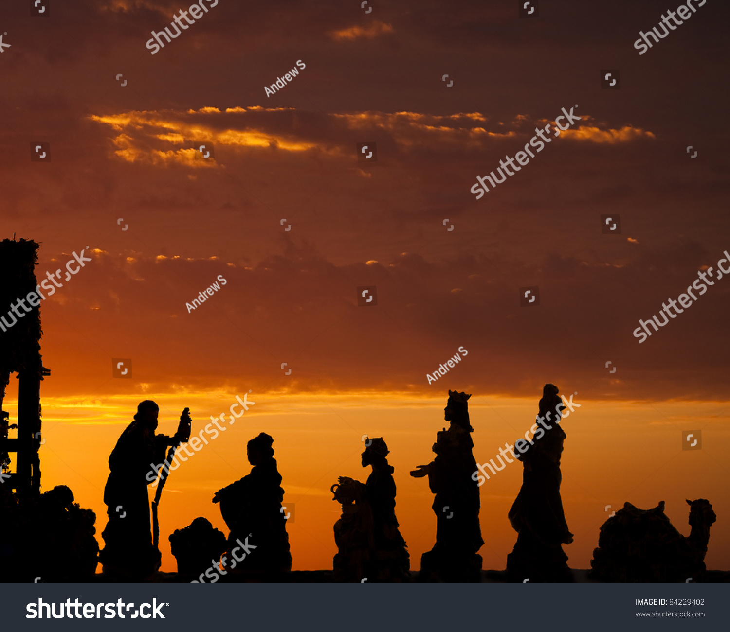 Nativity scene with wise men set against a dramatic sunrise stock