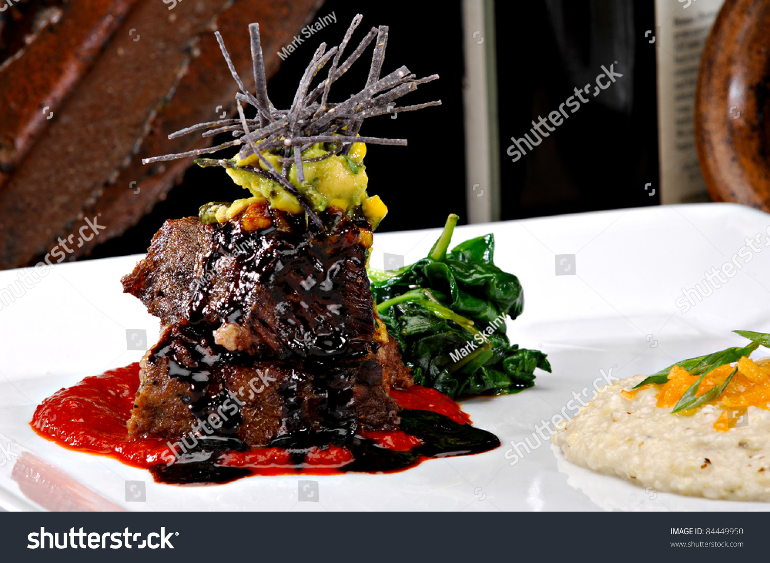 Stacked braised short ribs on a red tomato sauce. Garnished with ...