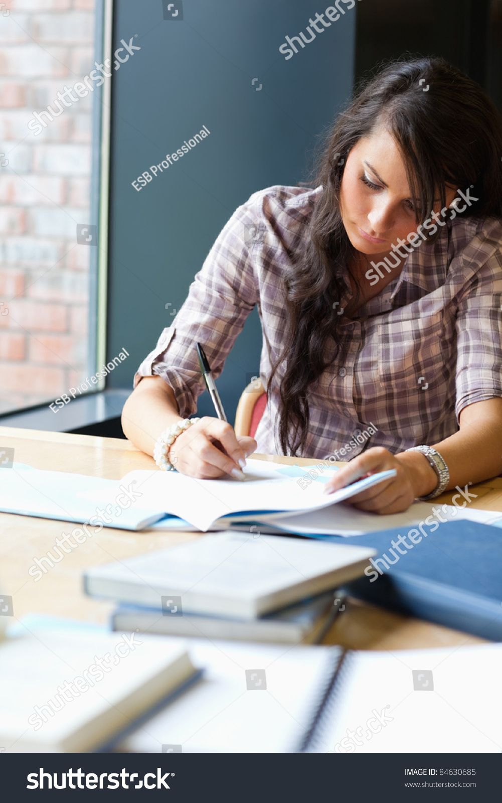 portrait beautiful student writing essay library stock photo portrait of a beautiful student writing an essay in a library