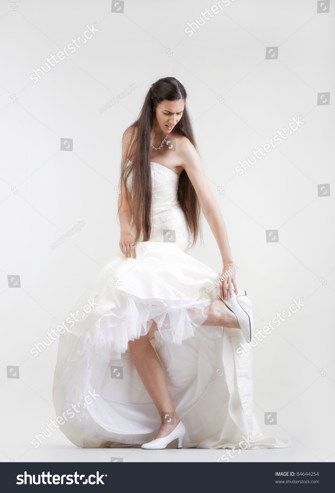 Bride In Wedding Dress Taking Off Her Shoe Checking Her ...