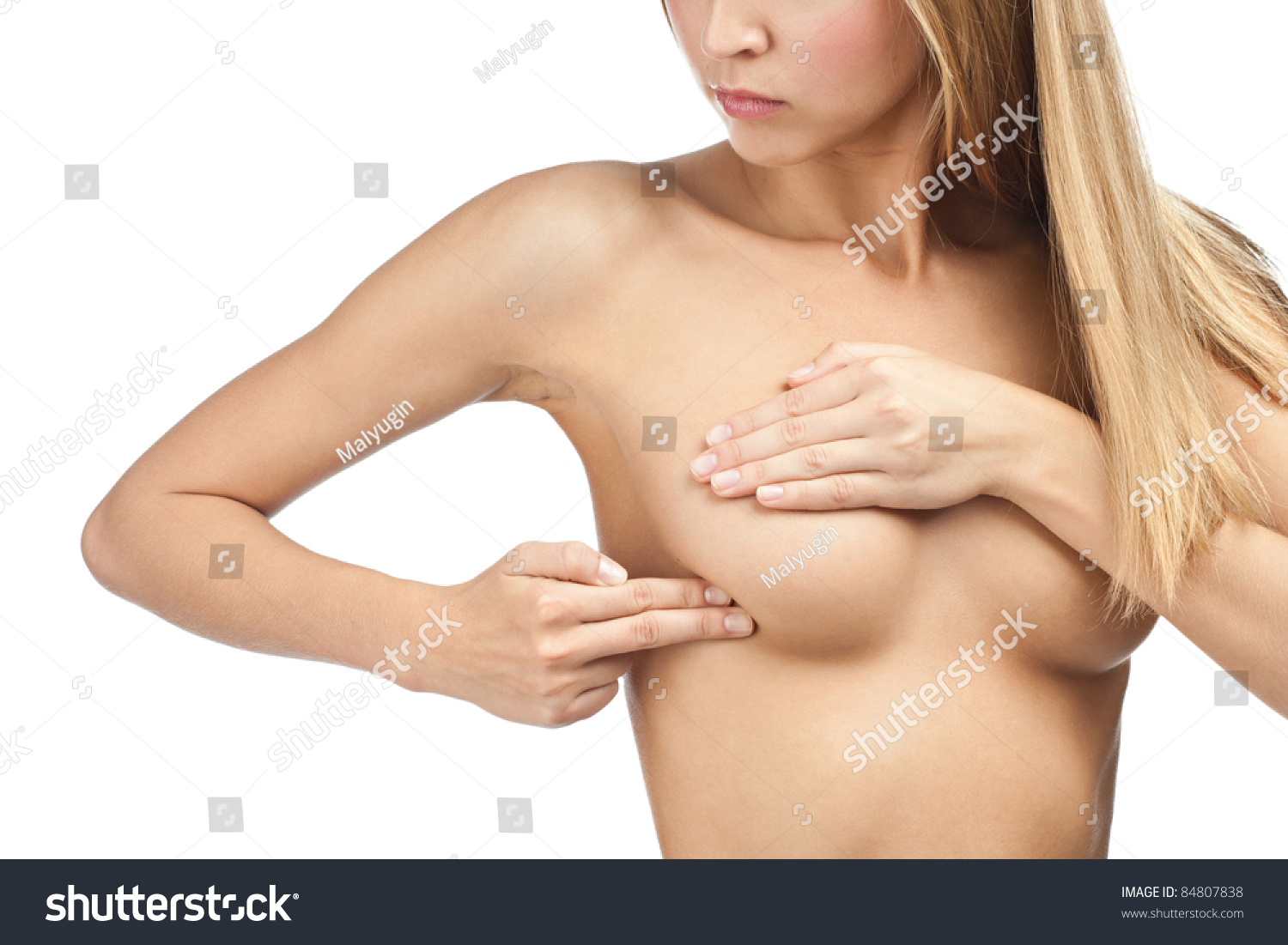 Young beautiful woman examining her breast for lumps or signs of breast cancer