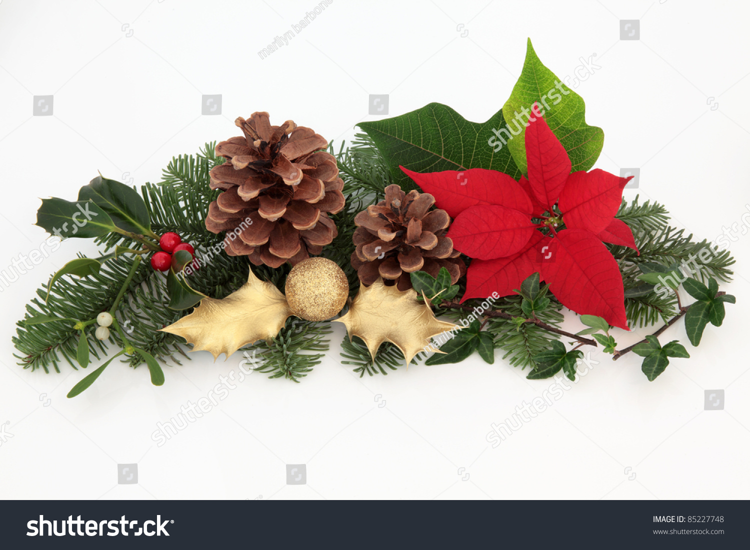 christmas decoration of red poinsettia flower mistletoe ivy gold holly and glitter bauble