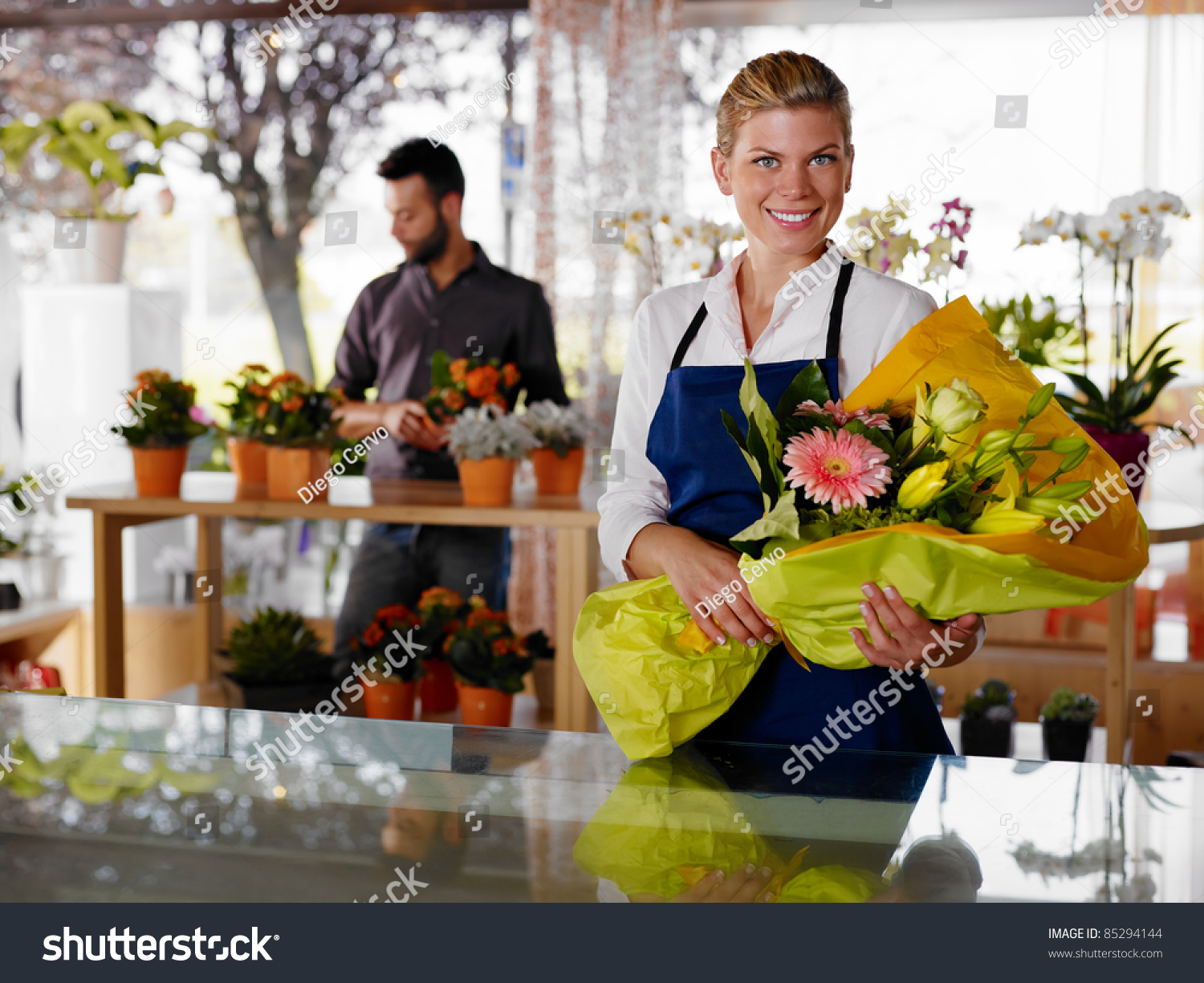 female s assistant working florist holding stock photo female s assistant working as florist and holding bouquet customer in background horizontal shape