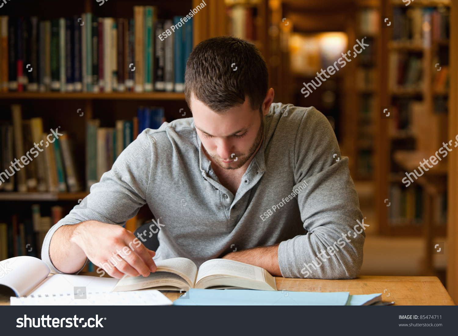 male student researching book library stock photo  male student researching a book in a library