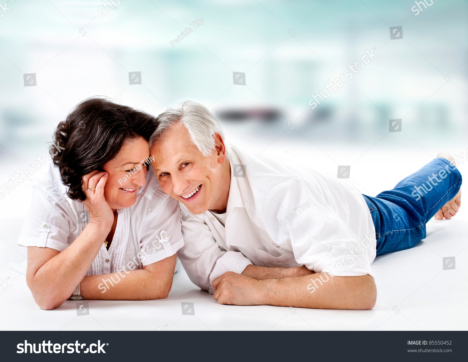 portrait of a sweet old couple smiling together on white