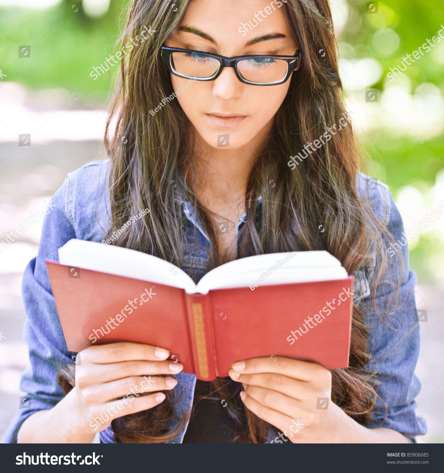 5c1e88a29eb646 Beautiful dark-haired serious girl in jeans jacket and glasses reads red  book against summer
