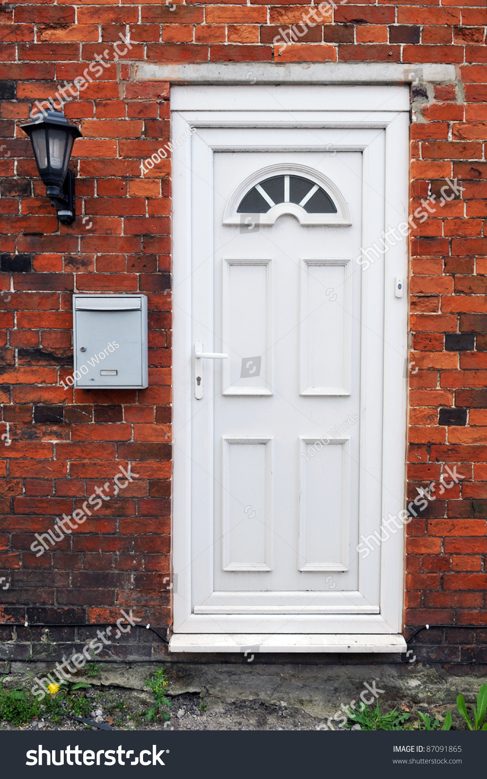 White Front Door Of A Red Brick English Town House Stock