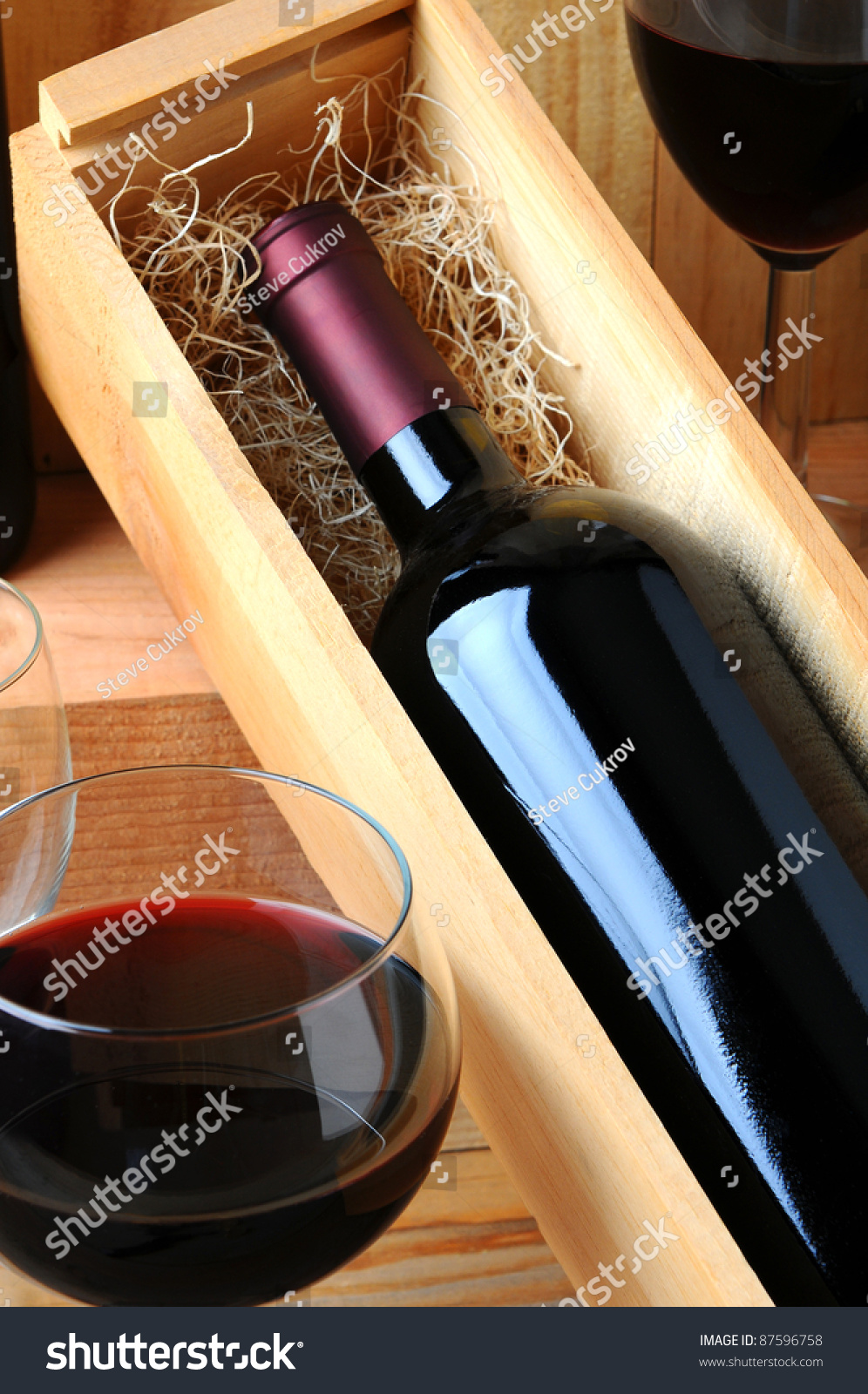 stock-photo-a-red-wine-bottle-in-a-woode