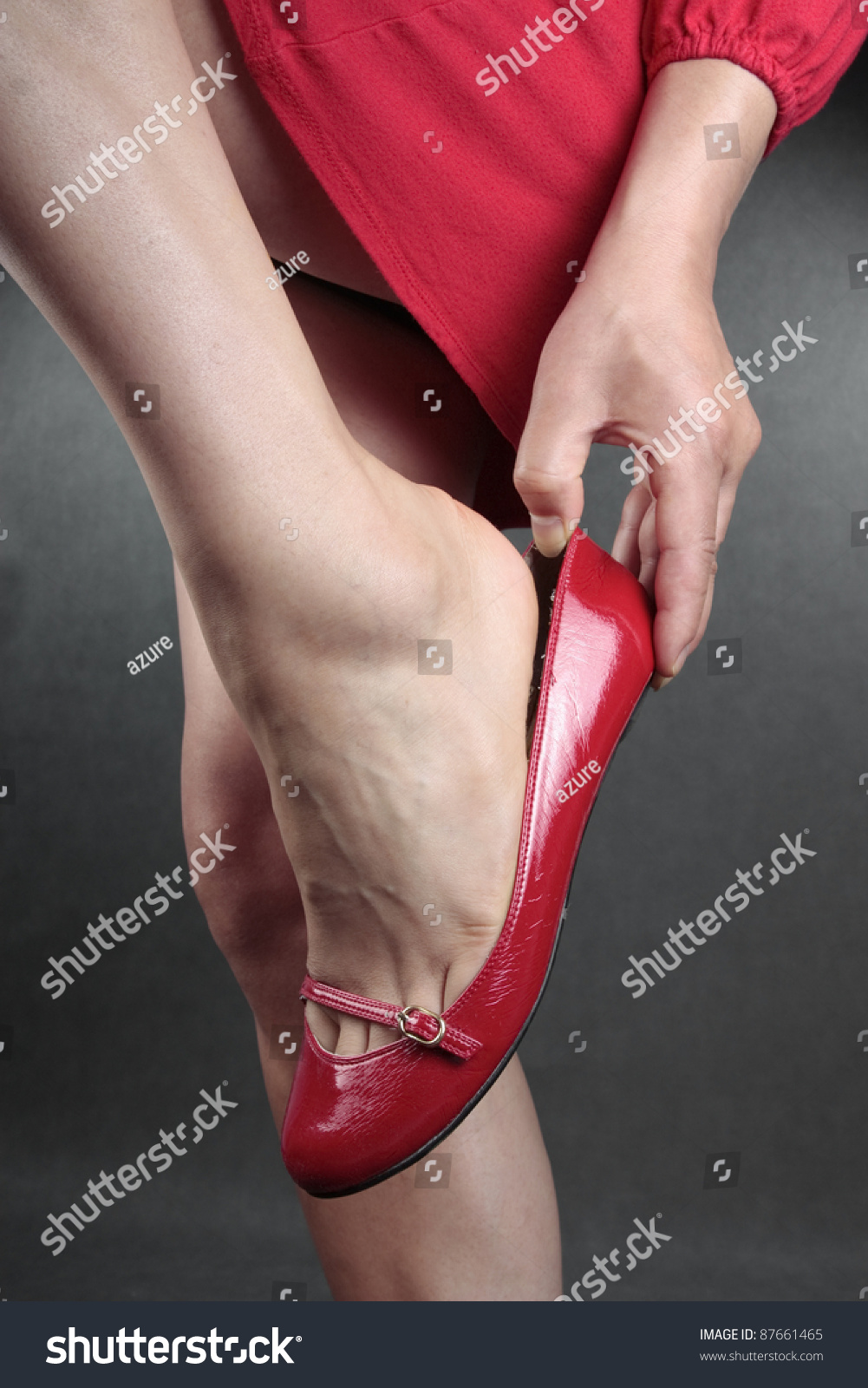 Woman Putting On Red Flat Shoes Over Grey Stock Photo