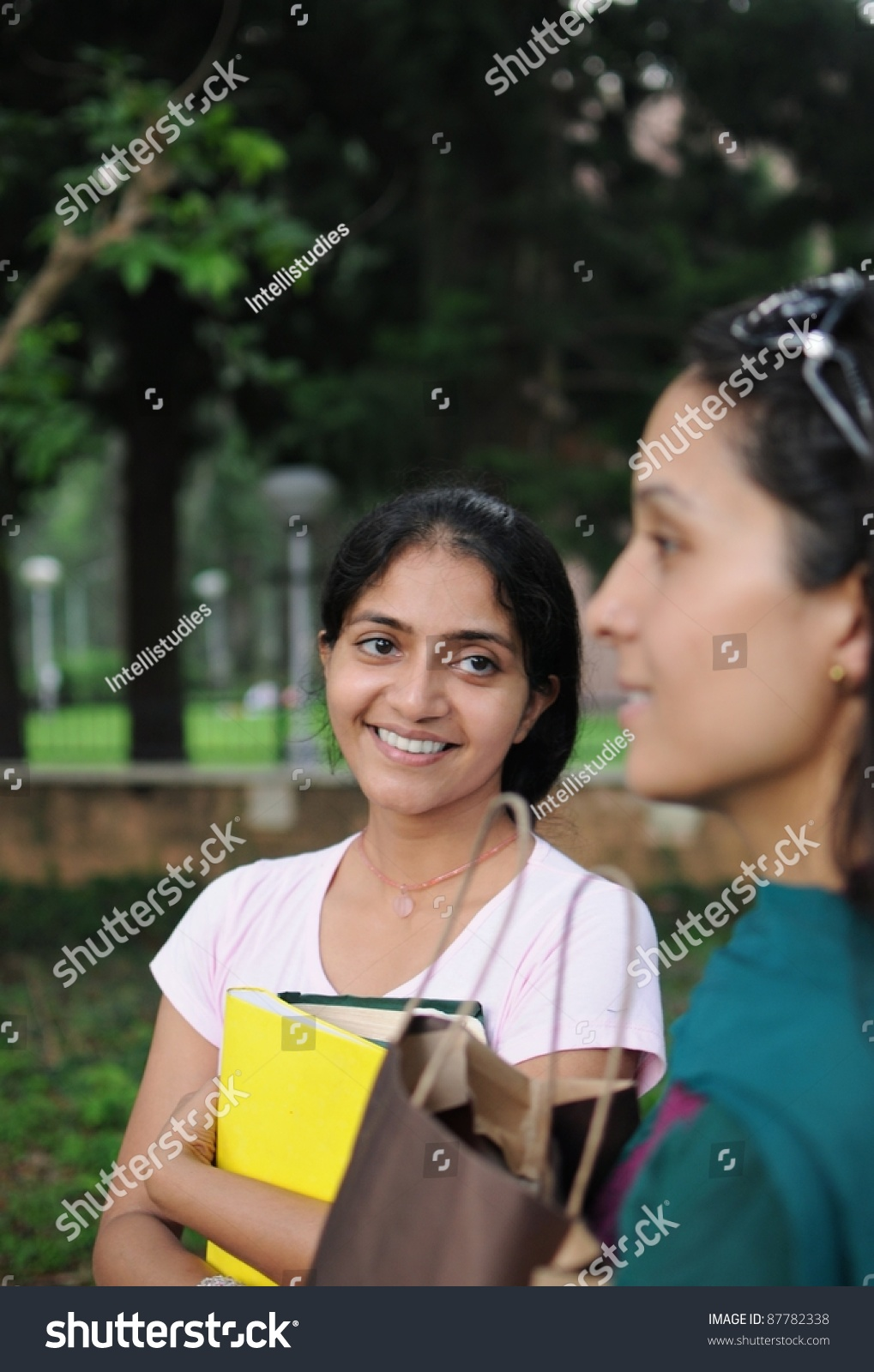 young indian college girl holding books stock photo (edit now