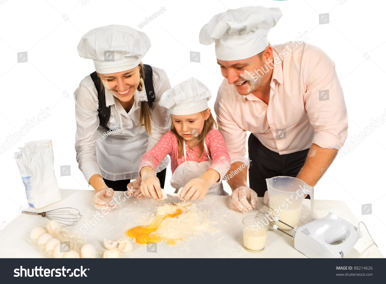 Happy family in kitchen - Happy Family Cooking Together In The Kitchen While Little Girl Adding Eggs In The Flour
