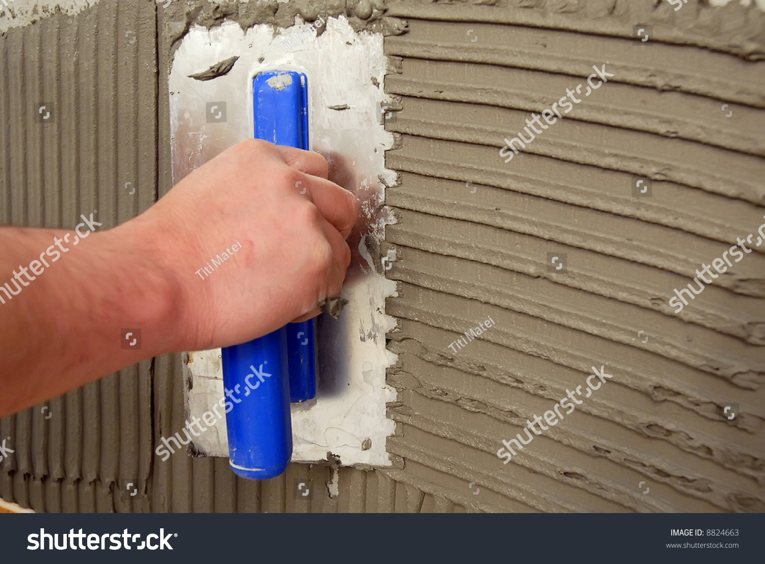 preparing a wall with adhesive for faience stock photo