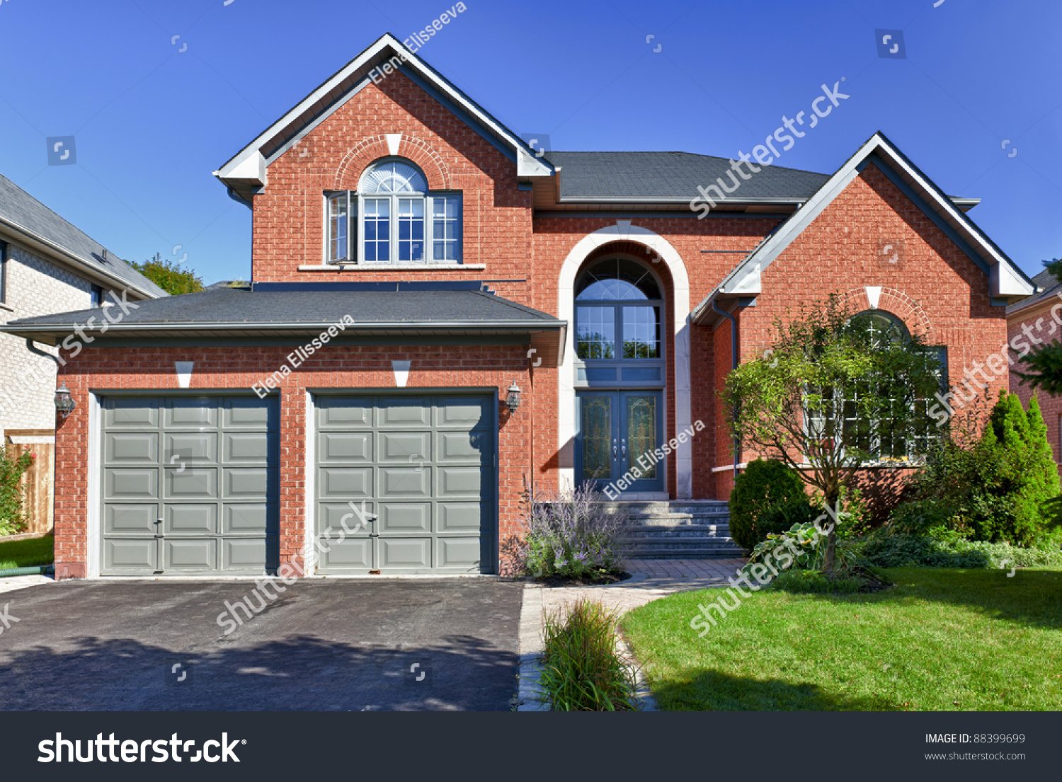 Brick house in suburbs with two car garage stock photo for Brick garages prices