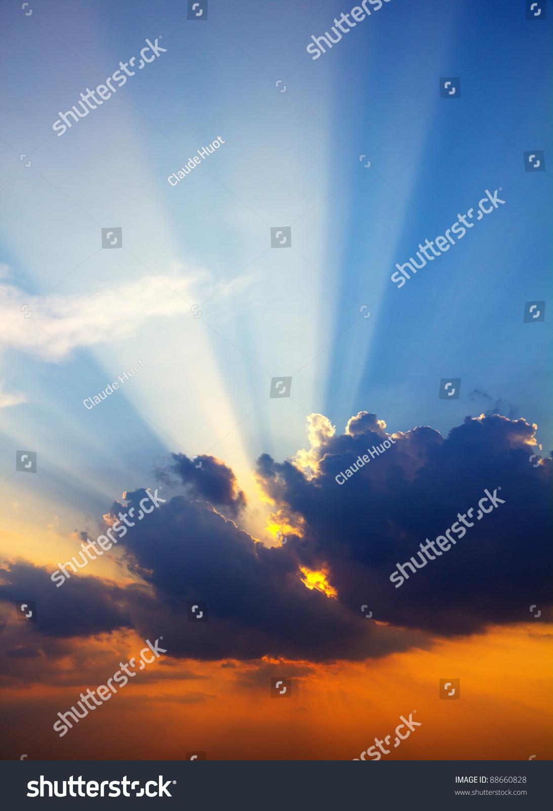 Sun rays through clouds at sunset