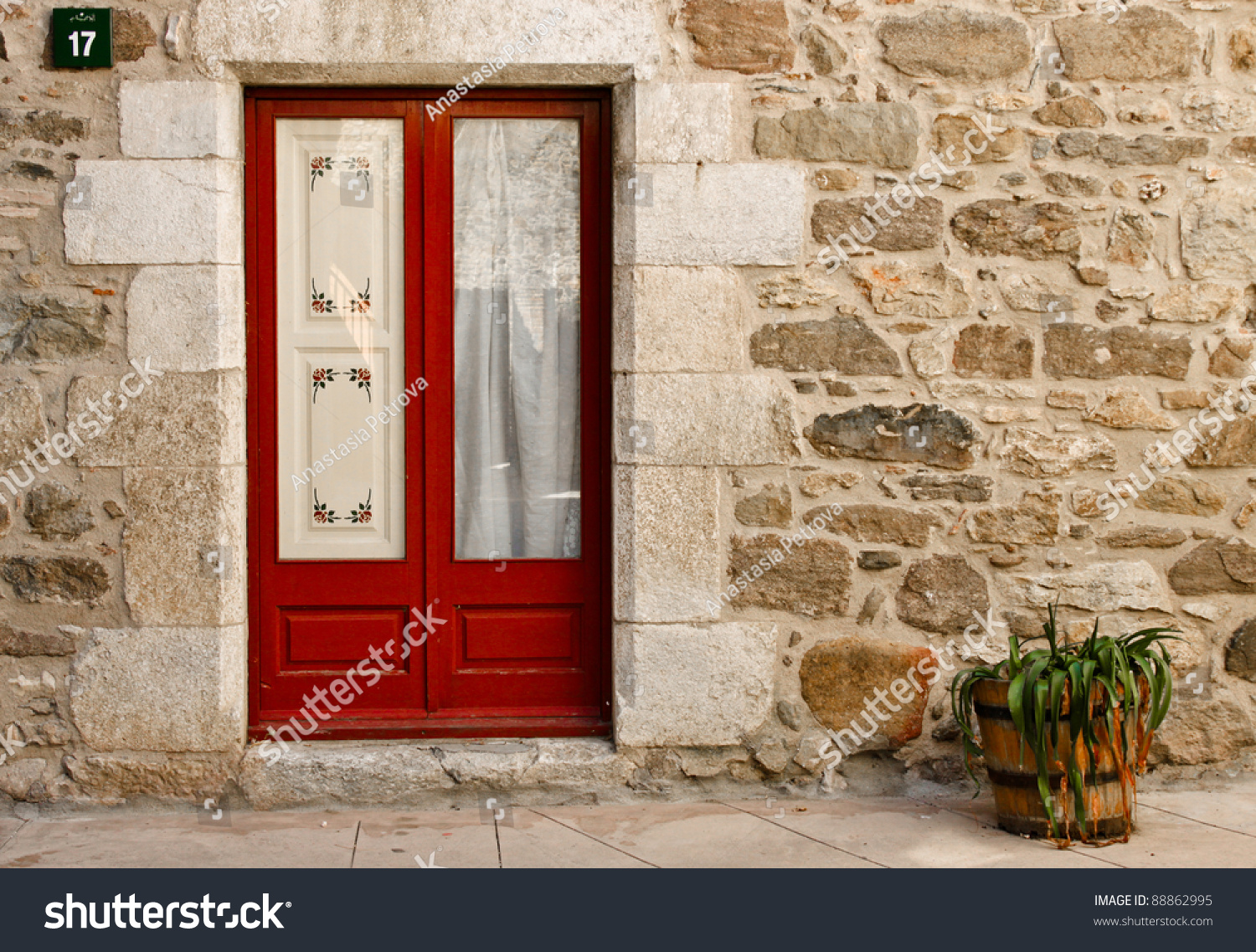 Red Doors Stone : A red door in stone house wall and flowerpot stock