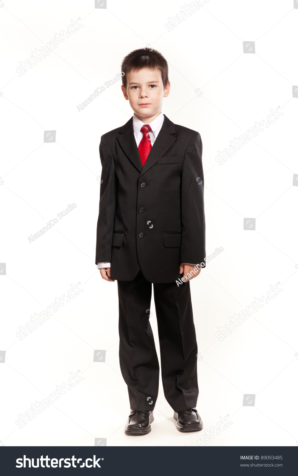d5705addb78c Young boy posing in studio in a black suit and a red tie, business code.
