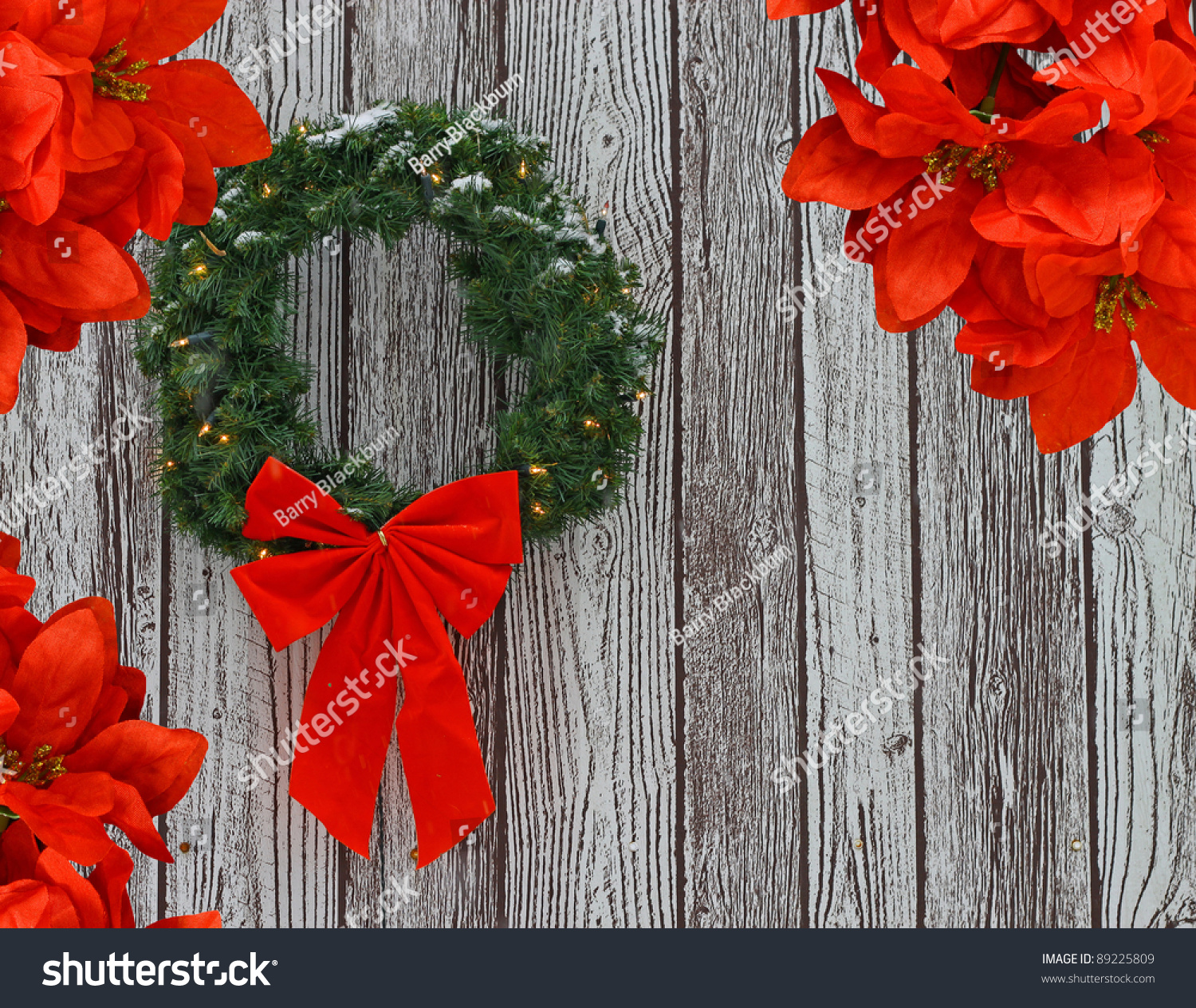 a snow covered lighted christmas wreath with a big red bow on it against a wooden pattern with poinsettias around it while it is snowing out for your use