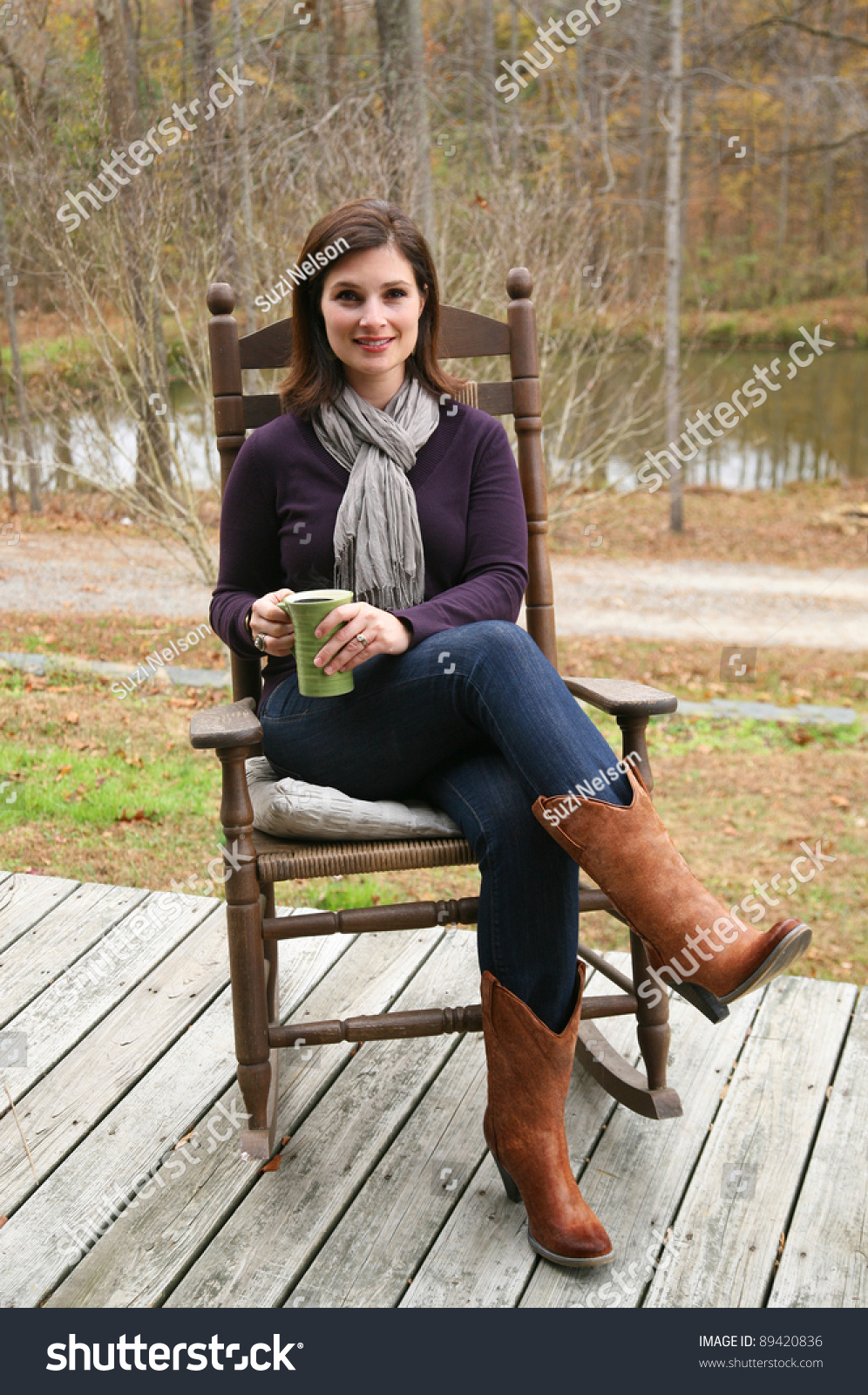 Fashionable Woman Relaxing In Rocking Chair On Porch