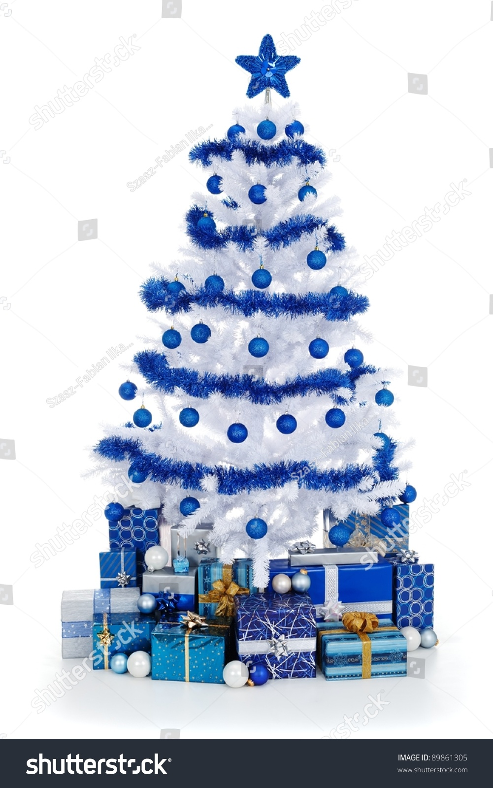 artificial white christmas tree on white decorated with blue ornaments and garland lots of