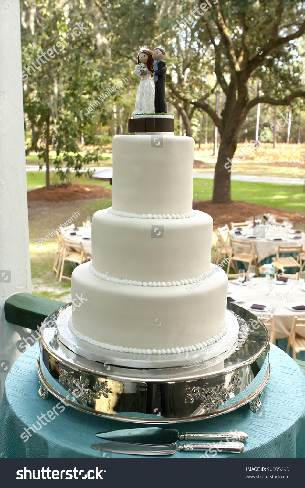 White Wedding Cake On Silver Tray At Outside Reception Stock Photo