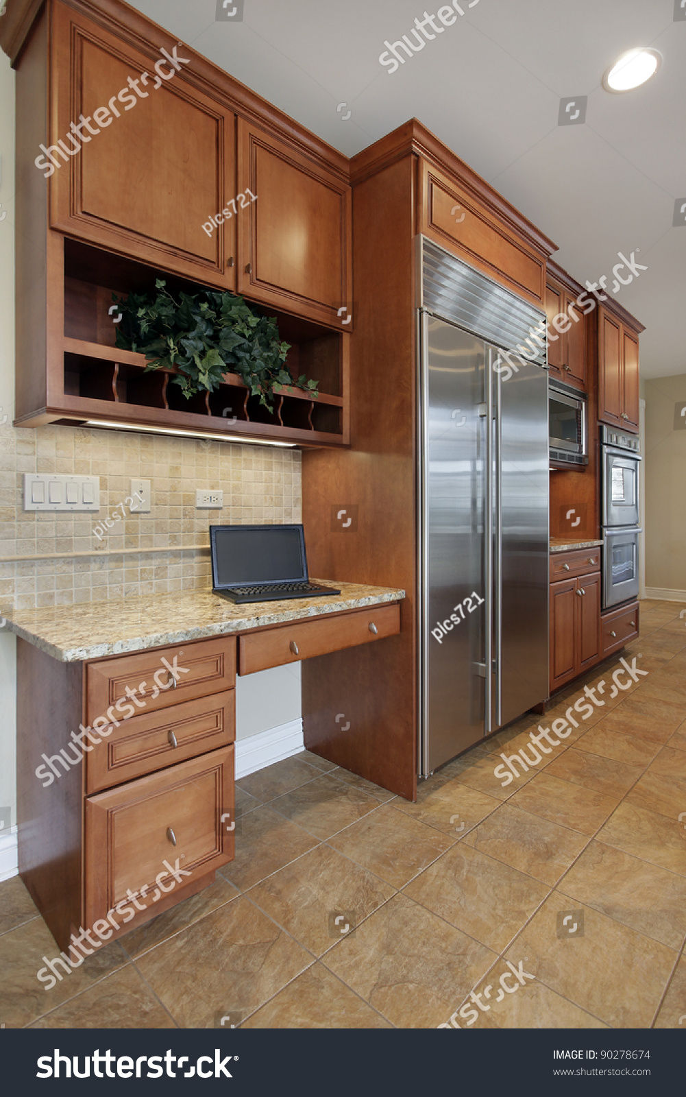 Kitchen Desk Area With Refrigerator And Wood Cabinetry