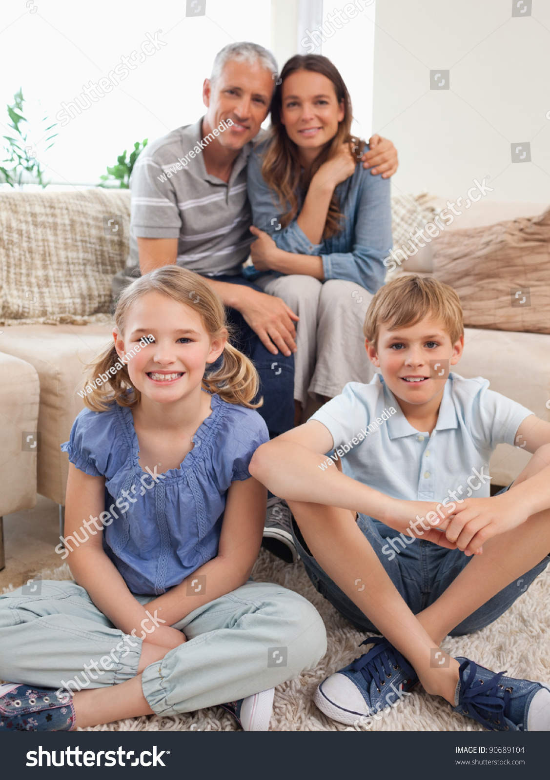 Portrait Of A Happy Family Posing In A Living Room Stock