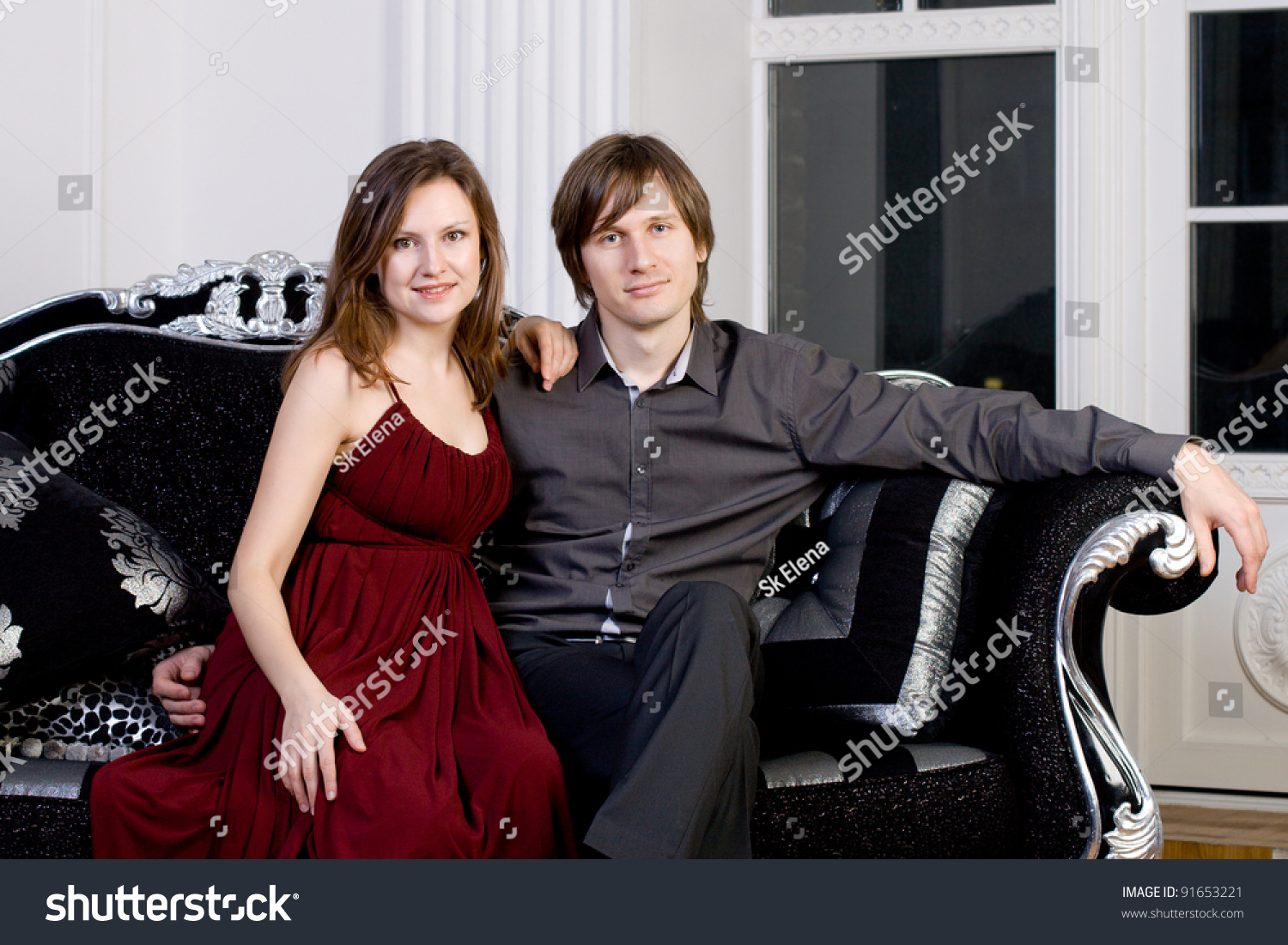 54dc889af922e Portrait of a young couple in elegant evening dresses sitting on vintage  chair