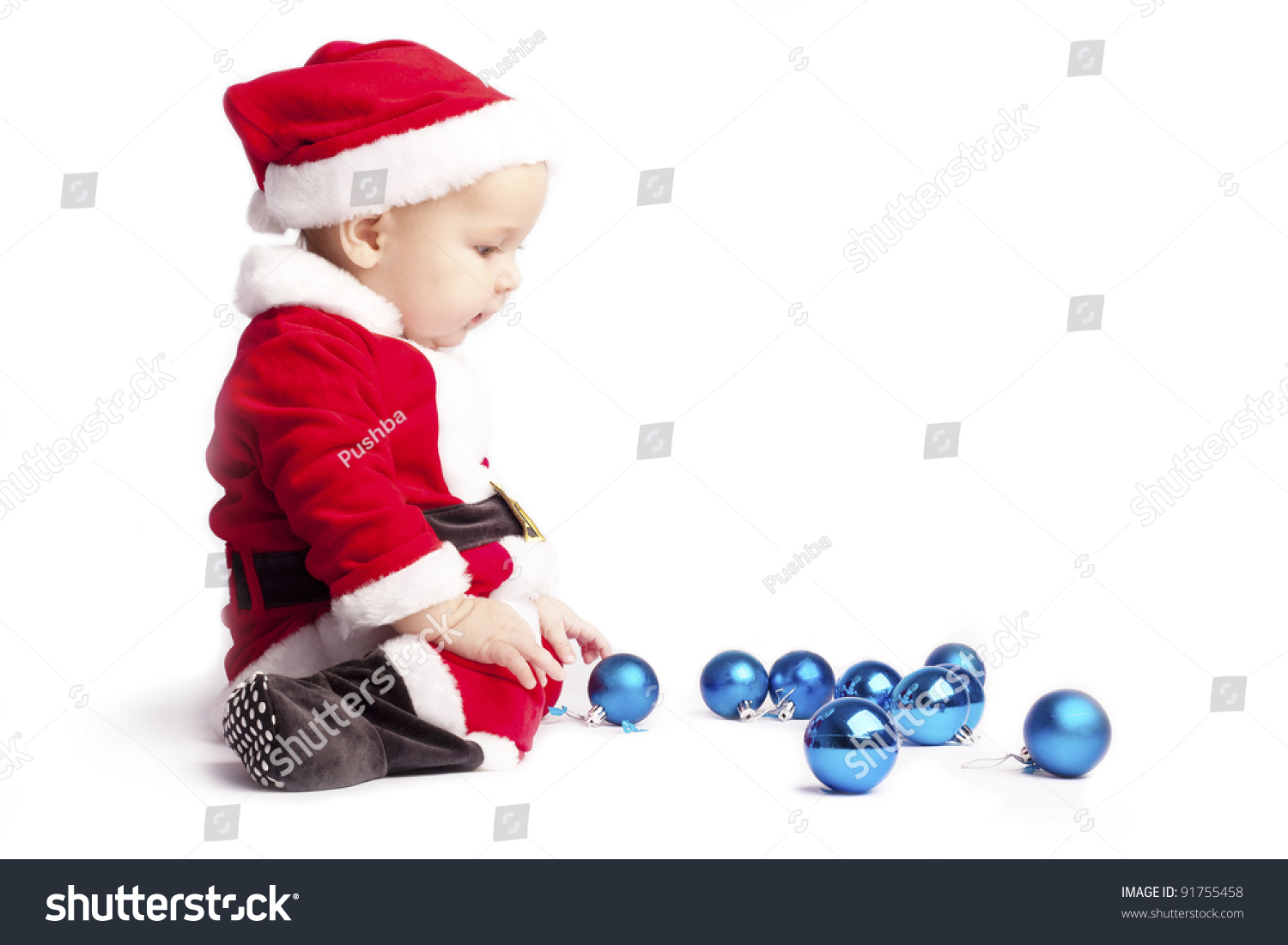 Sad Little Baby Boy Santa Sits And Stares At The Blue Christmas Balls On White Background Put ...