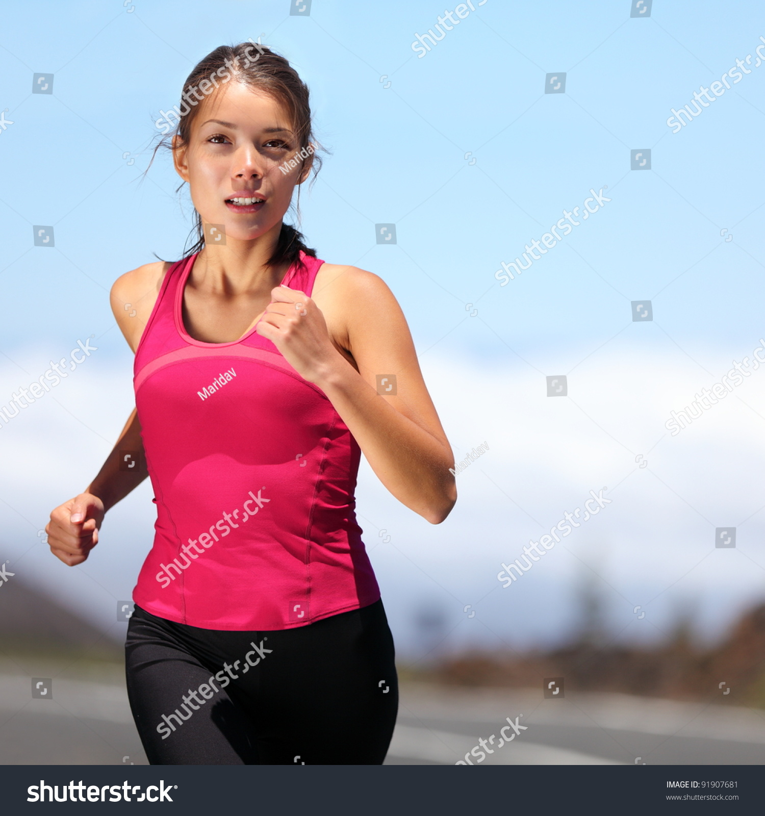 runner woman running outdoors training marathon stock