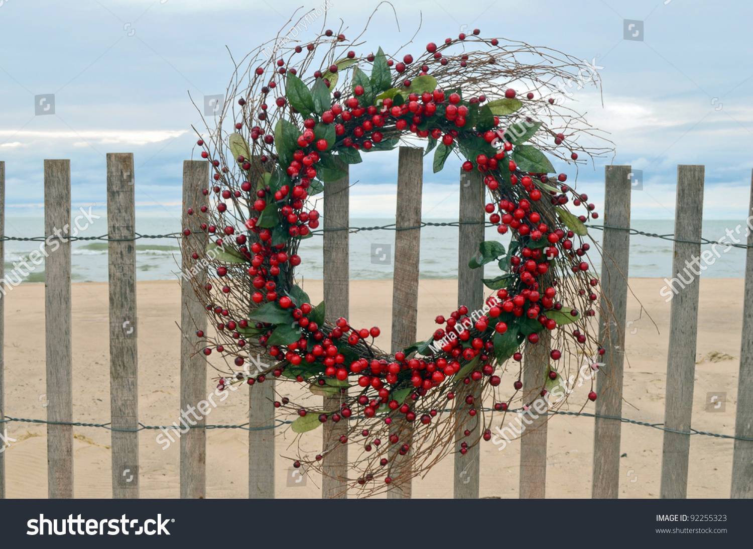 christmas wreath with red berries hanging on a beach fence - Beach Christmas Wreath