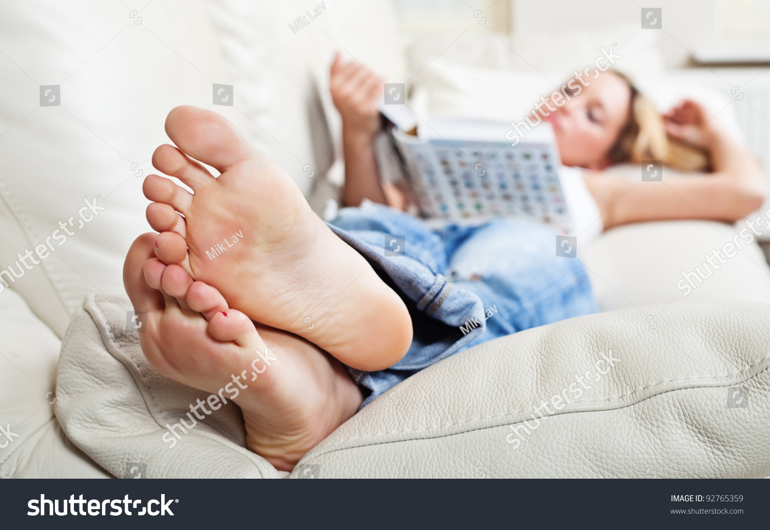 Barefoot Young Woman Lying On Sofa And Reading Book Shallow Depth Of Field Focus