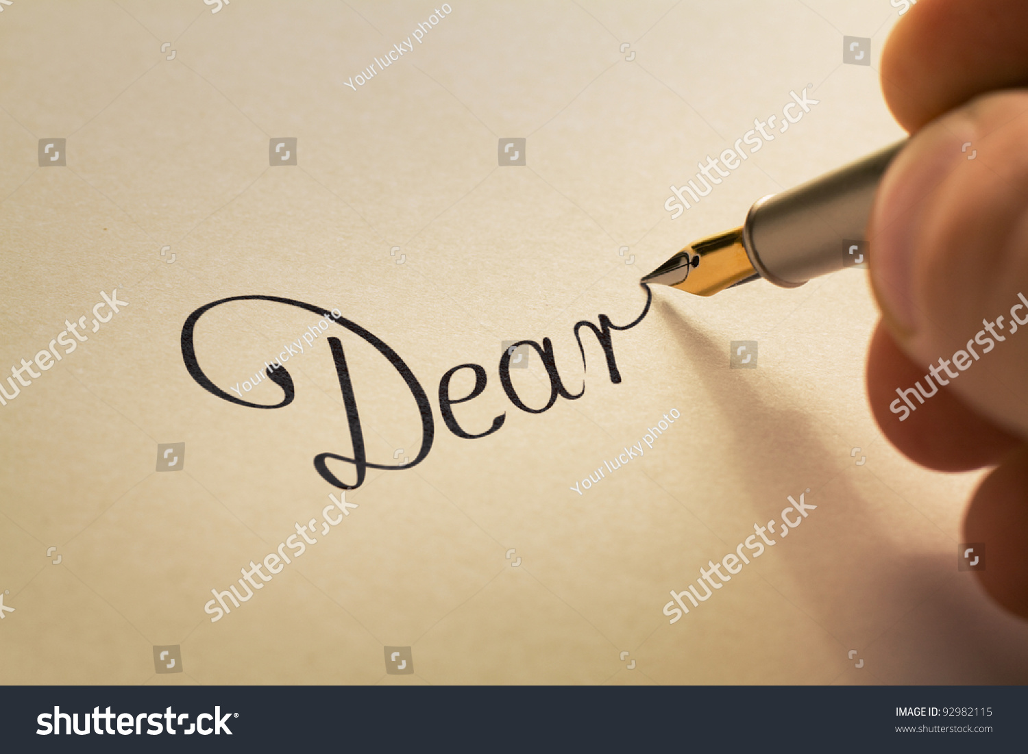 Hand writing calligraphic letter starting dear stock photo royalty hand is writing calligraphic letter starting with dear using old pen on yellow paper thecheapjerseys Image collections