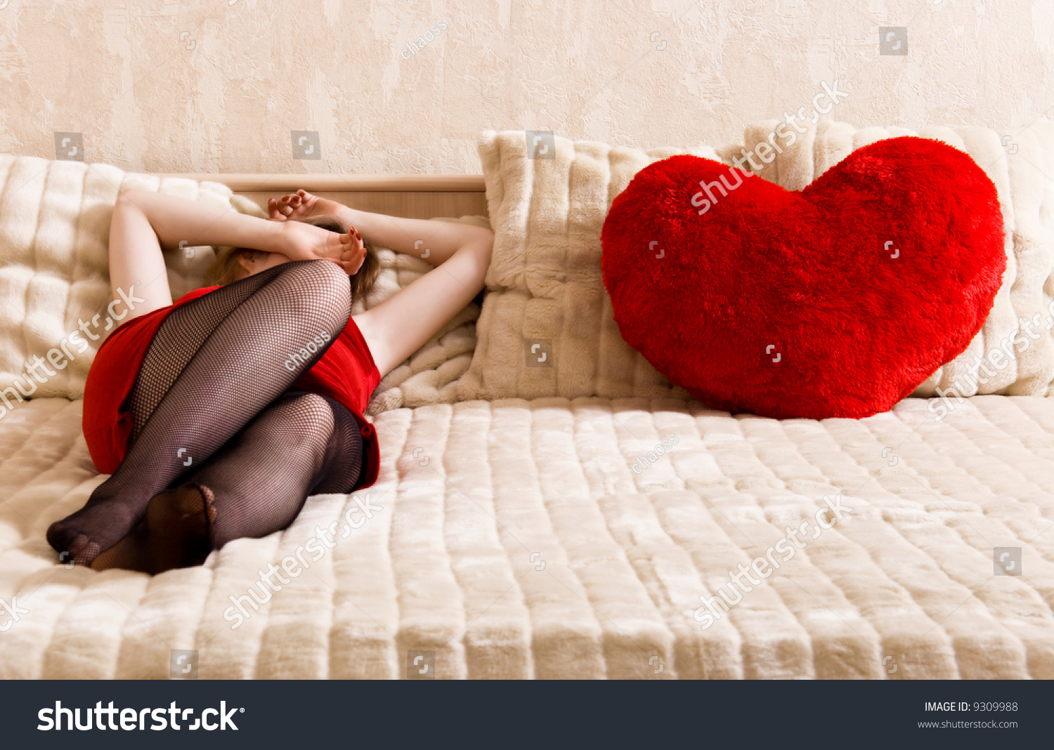 young woman resting on a bed and heart shaped pillow concept image about unrequited love