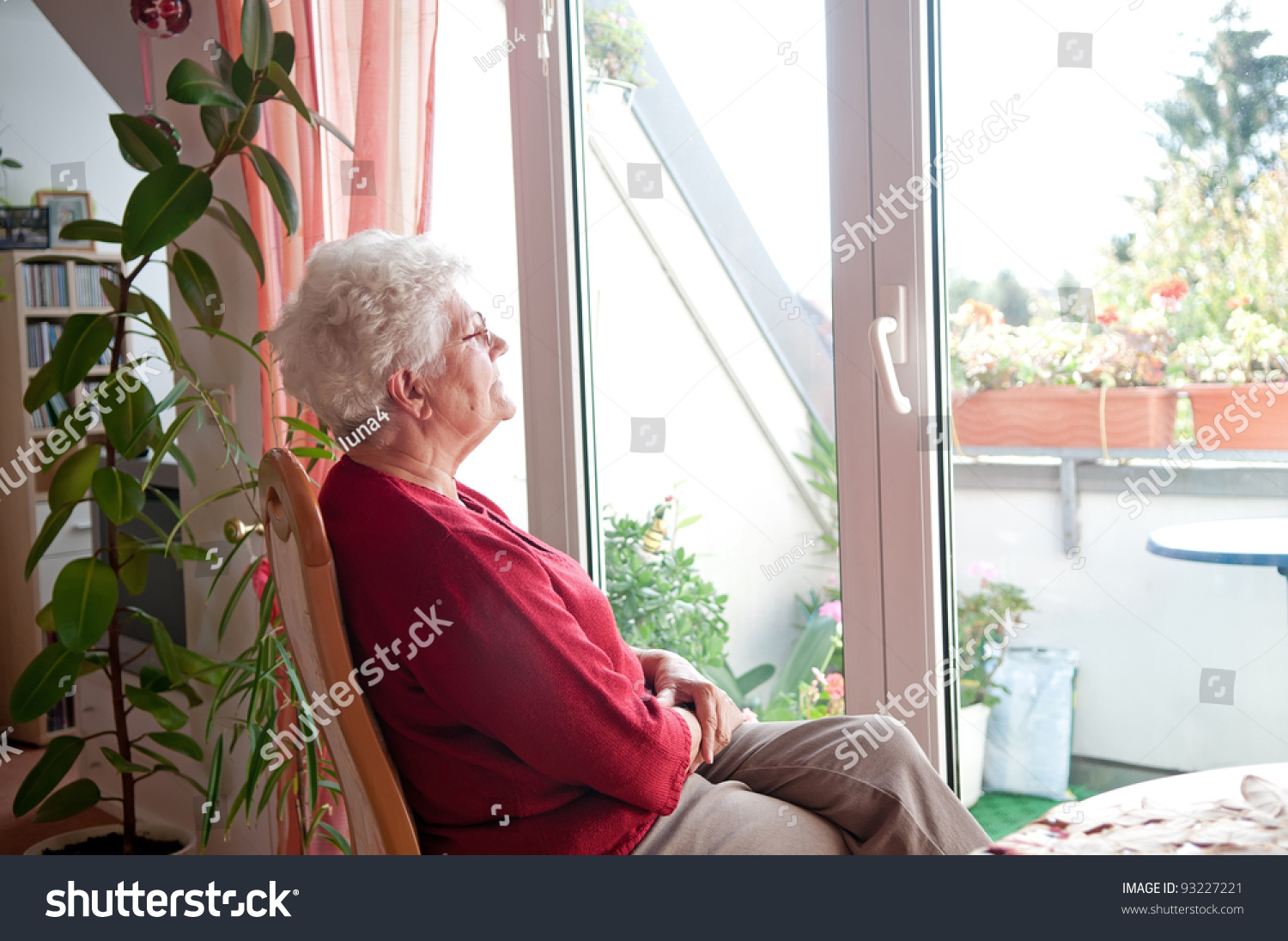 lonely old woman looks out the window #93227221