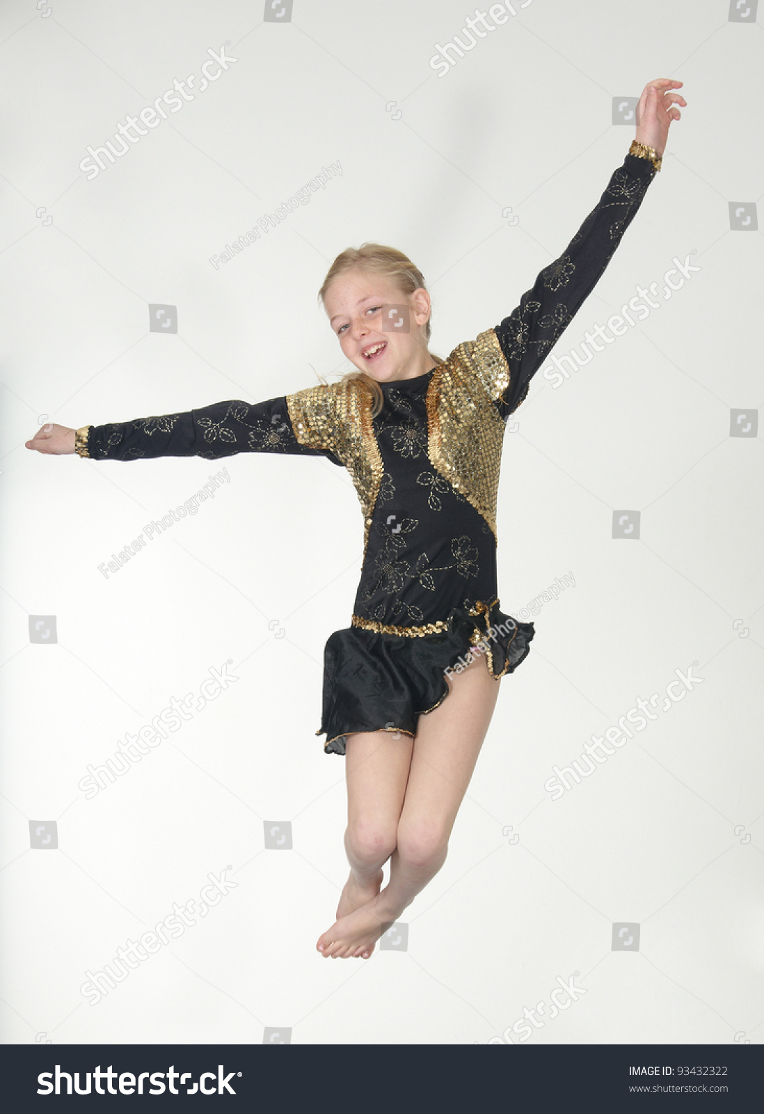 black preteen Preteen blond girl in black and gold leotard costume jumping for joy into  the air isolated