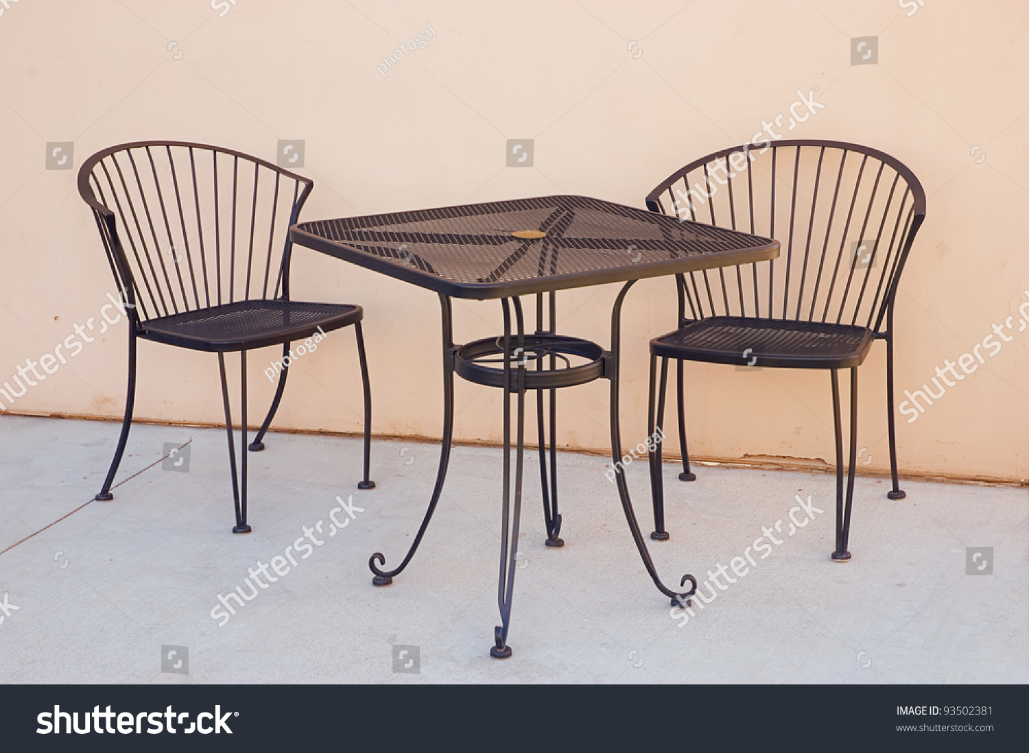 Wrought iron table and chairs outside sidewalk cafe for Wrought iron cafe chairs