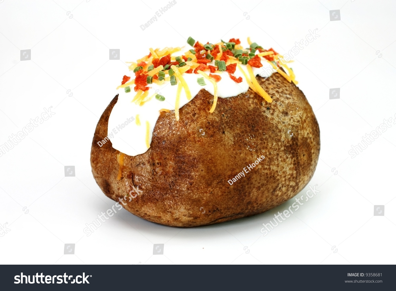 Baked potato loaded with butter, sour cream, cheddar cheese, bacon ...
