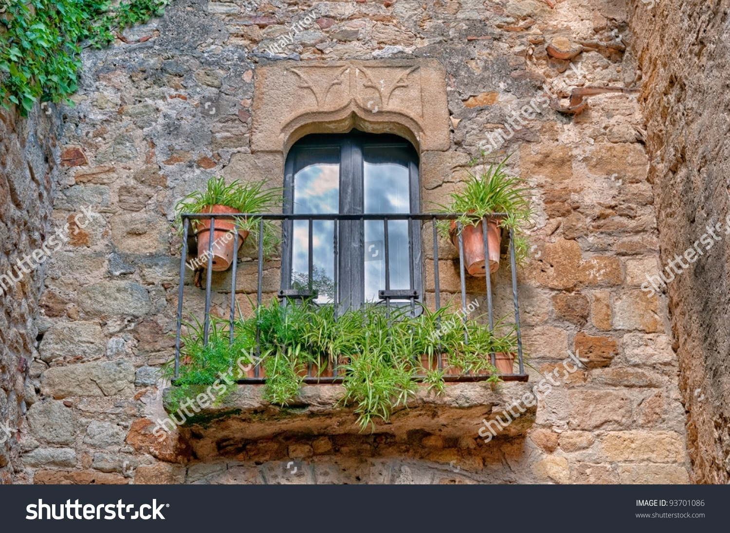 Balcony In Marble Wall : Small balcony with flowers on a stone wall in peratallada