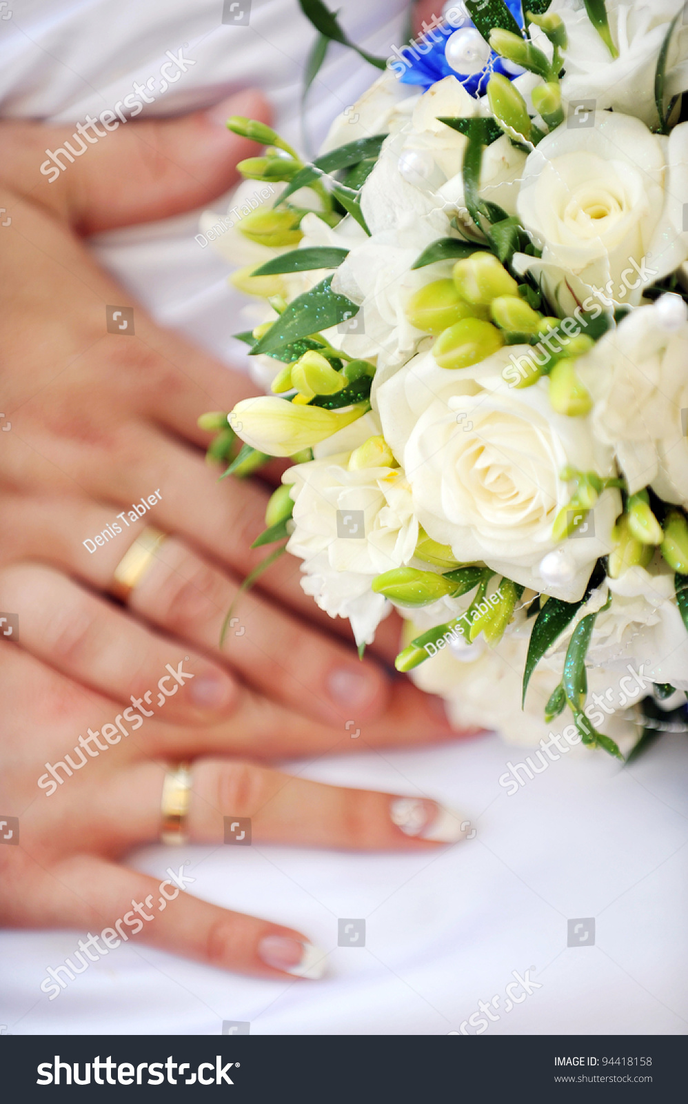 two hands with wedding rings and flowers stock photo