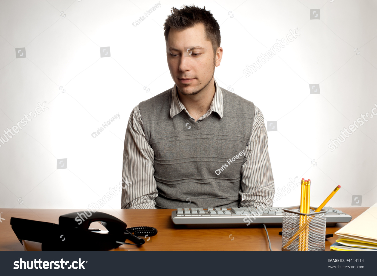 Frustrated office worker on the phone holding stock photo image - An Office Worker Waiting For The Phone To Ring