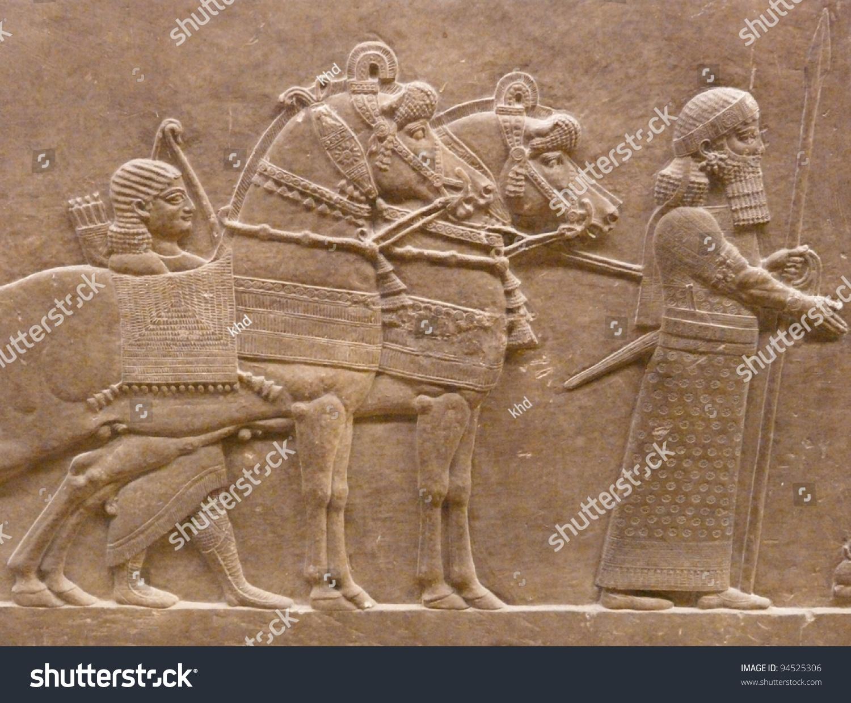 Ancient assyrian wall carvings men horses stock photo