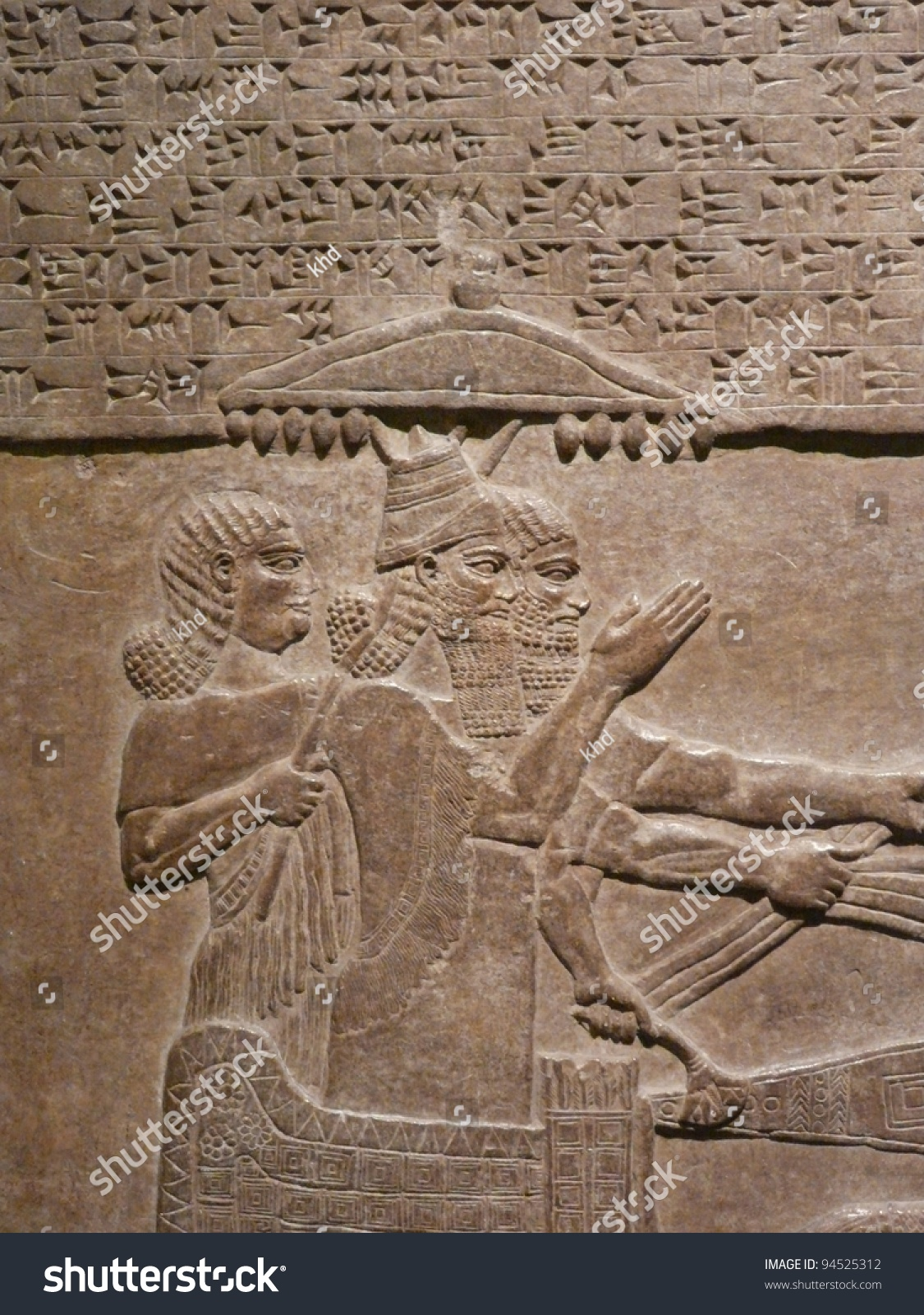 Ancient assyrian wall carvings of men and cuneiform